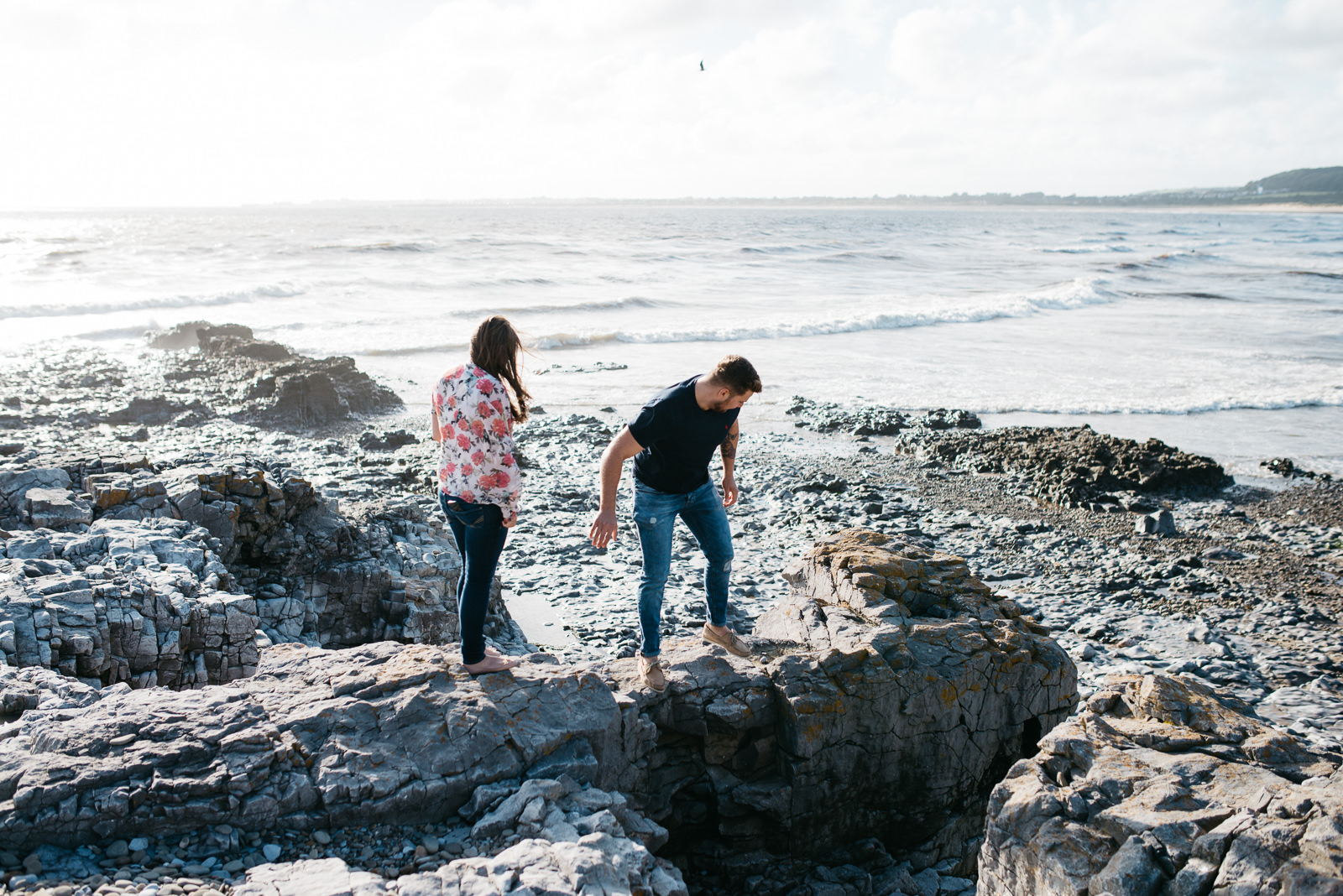 Couple steadying themselves on the rocks at the beach at Ogmore
