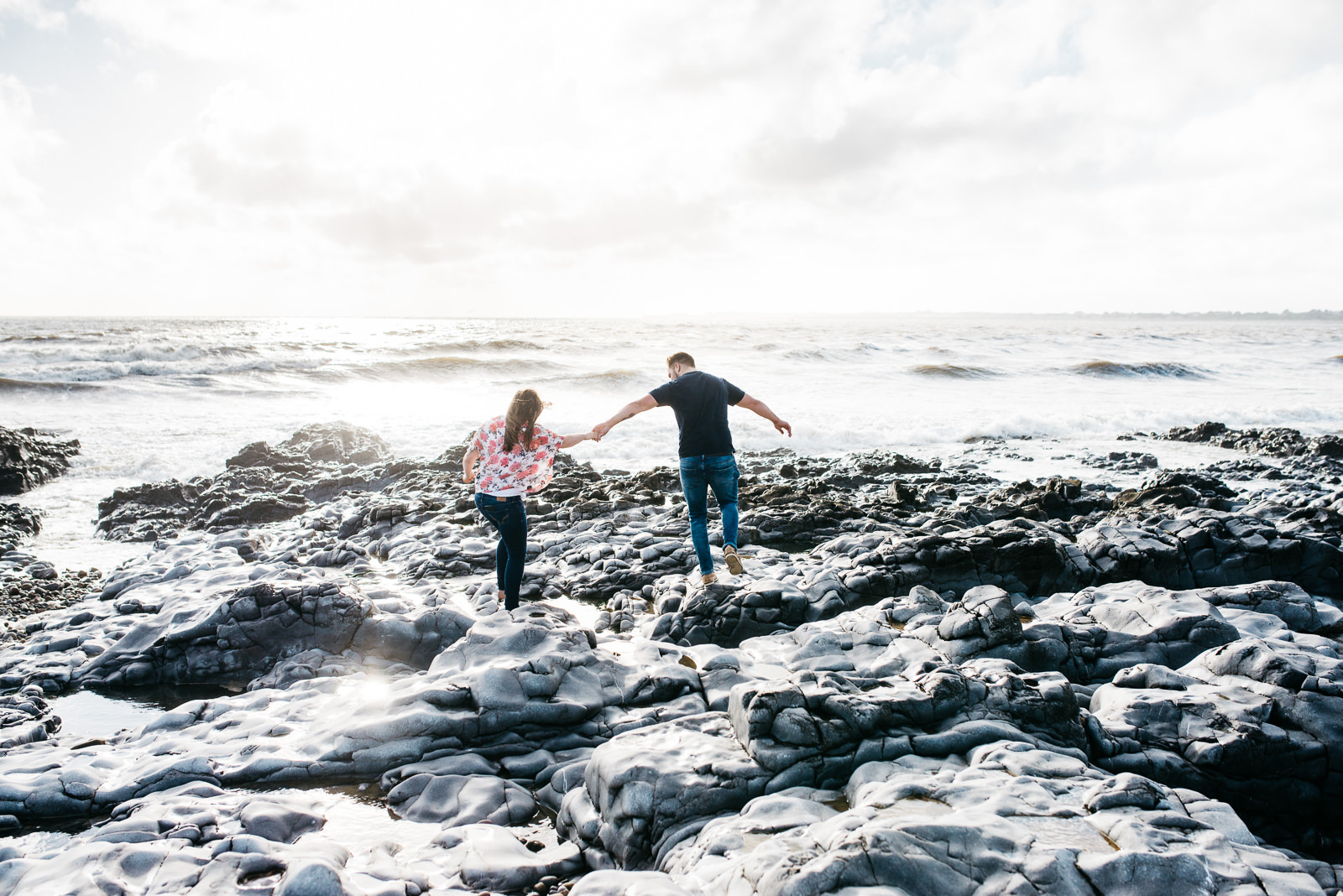 Couple climbing over the rocks at Ogmore-by-Sea
