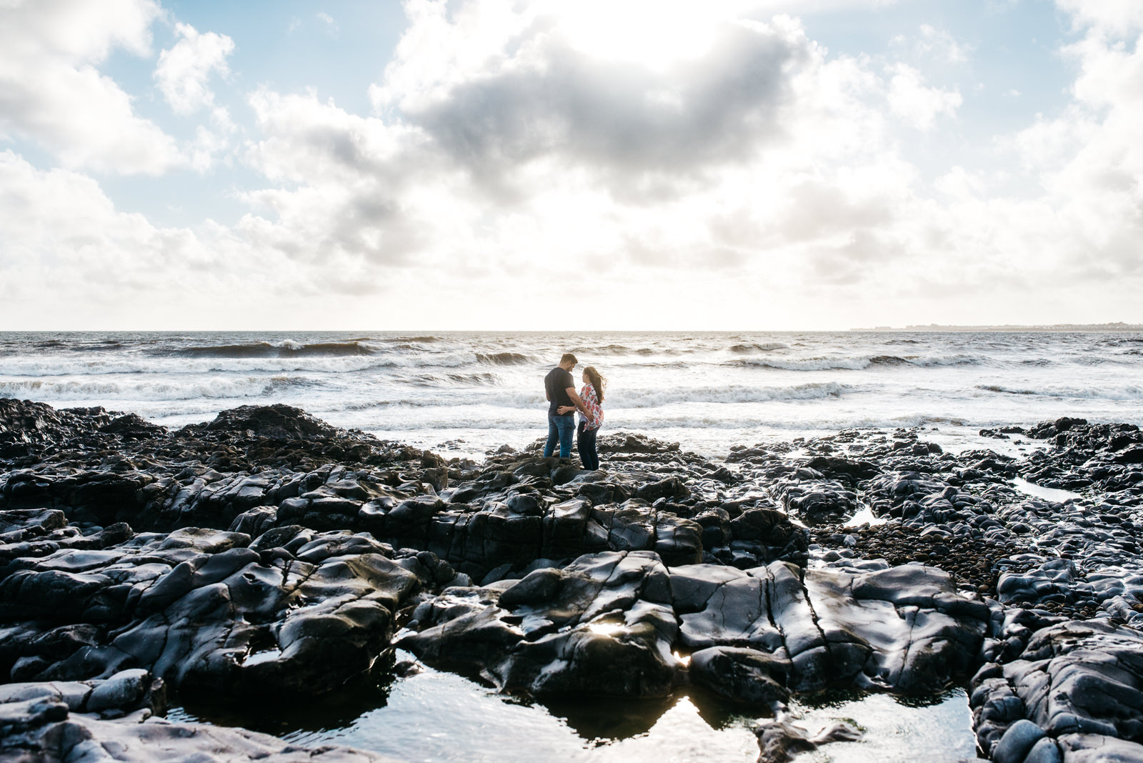 Couple standing on rocks at Ogmore-by-sea during their pre-wedding photograph session