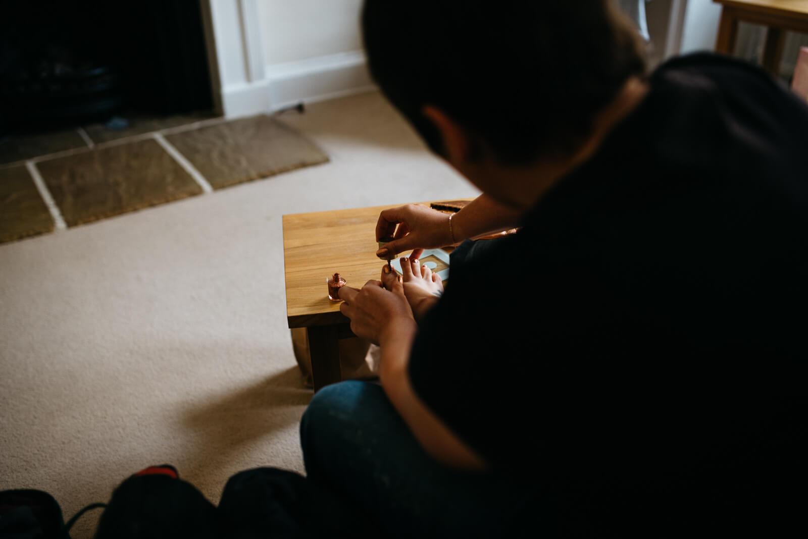 Bridesmaid painting toe nails during bridal prep