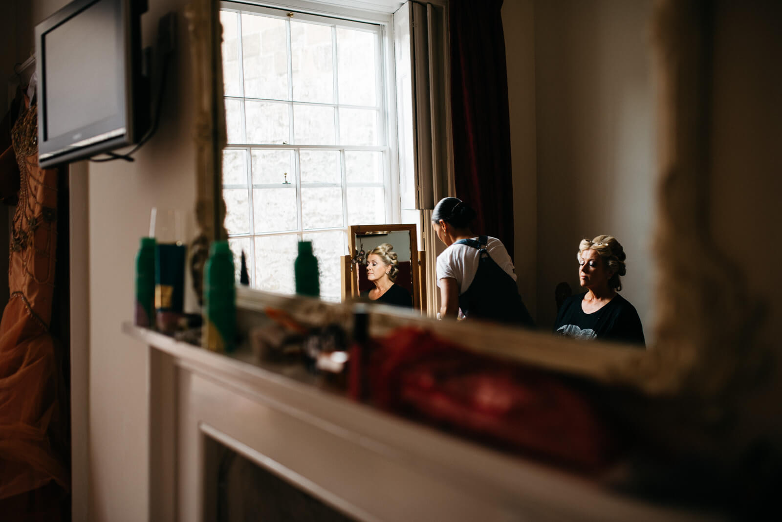 Bride in rollers having finishing touches done to her make up at the Courtyard Apartments being heading to her Roman Baths ceremony