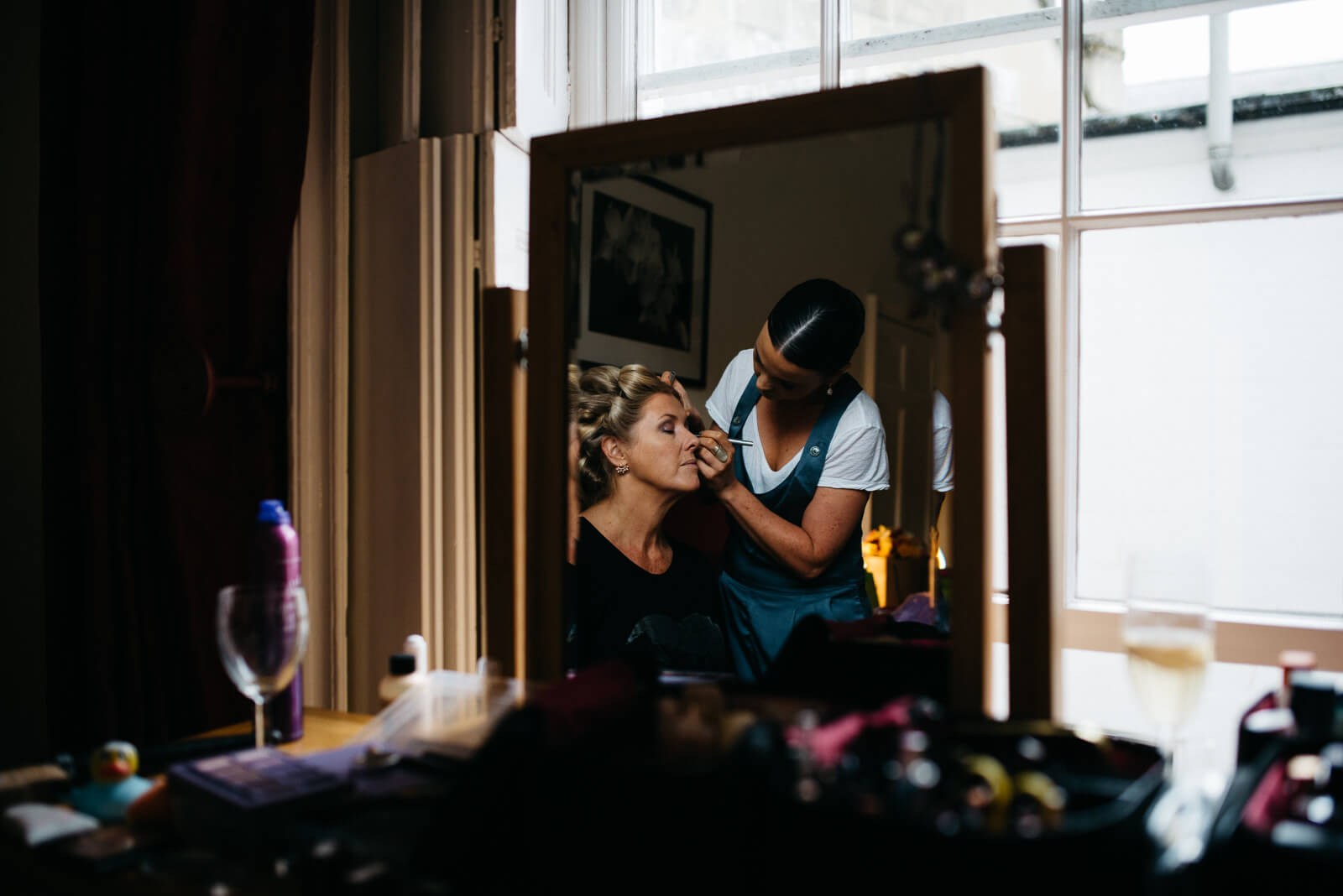 Makeup artist doing brides makeup in apartment