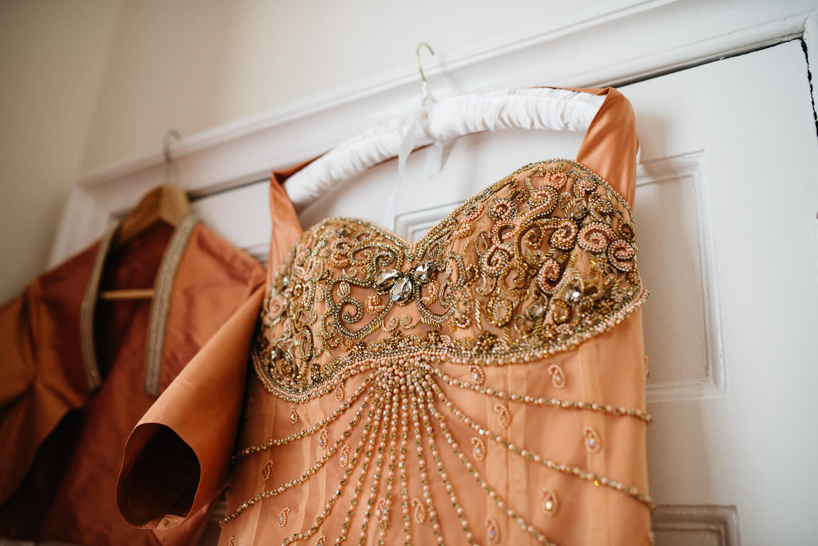 Gold embellished wedding dress hanging on fabric covered hanger