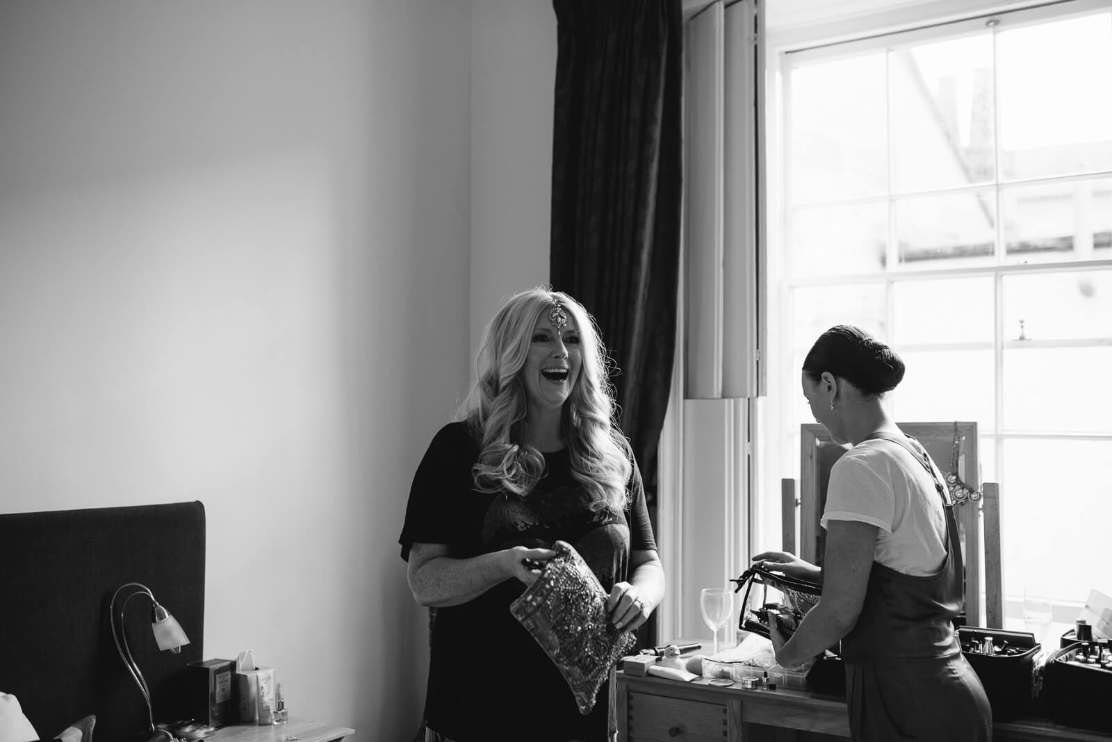 Bride laughing before getting dressed at the Courtyard apartments before her Roman Baths ceremony