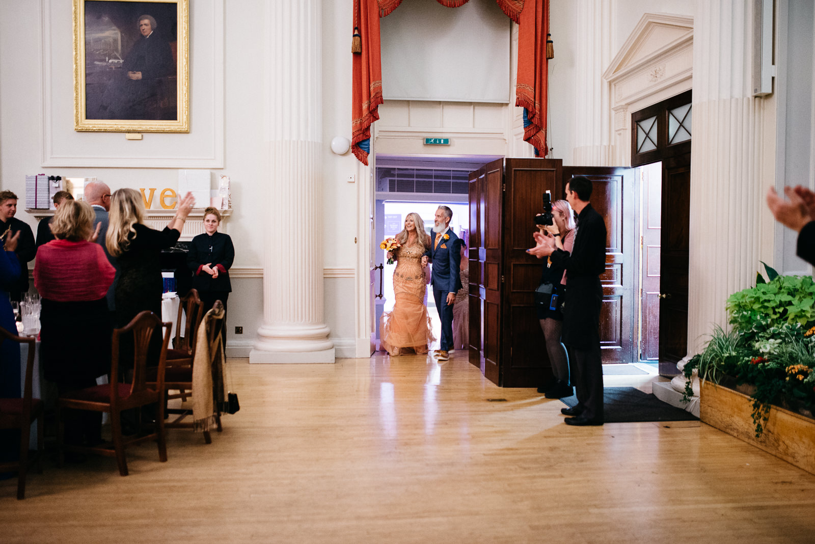 Bride and groom make entrance into the Pump House greeted by their guests