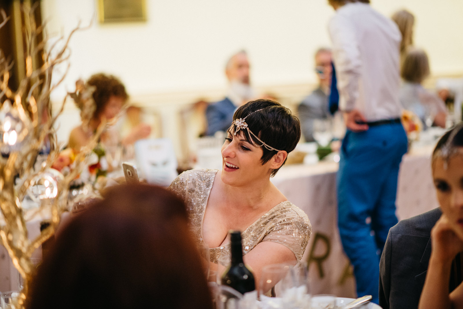Stylish bridesmaid smiling during wedding breakfast at the Pump House