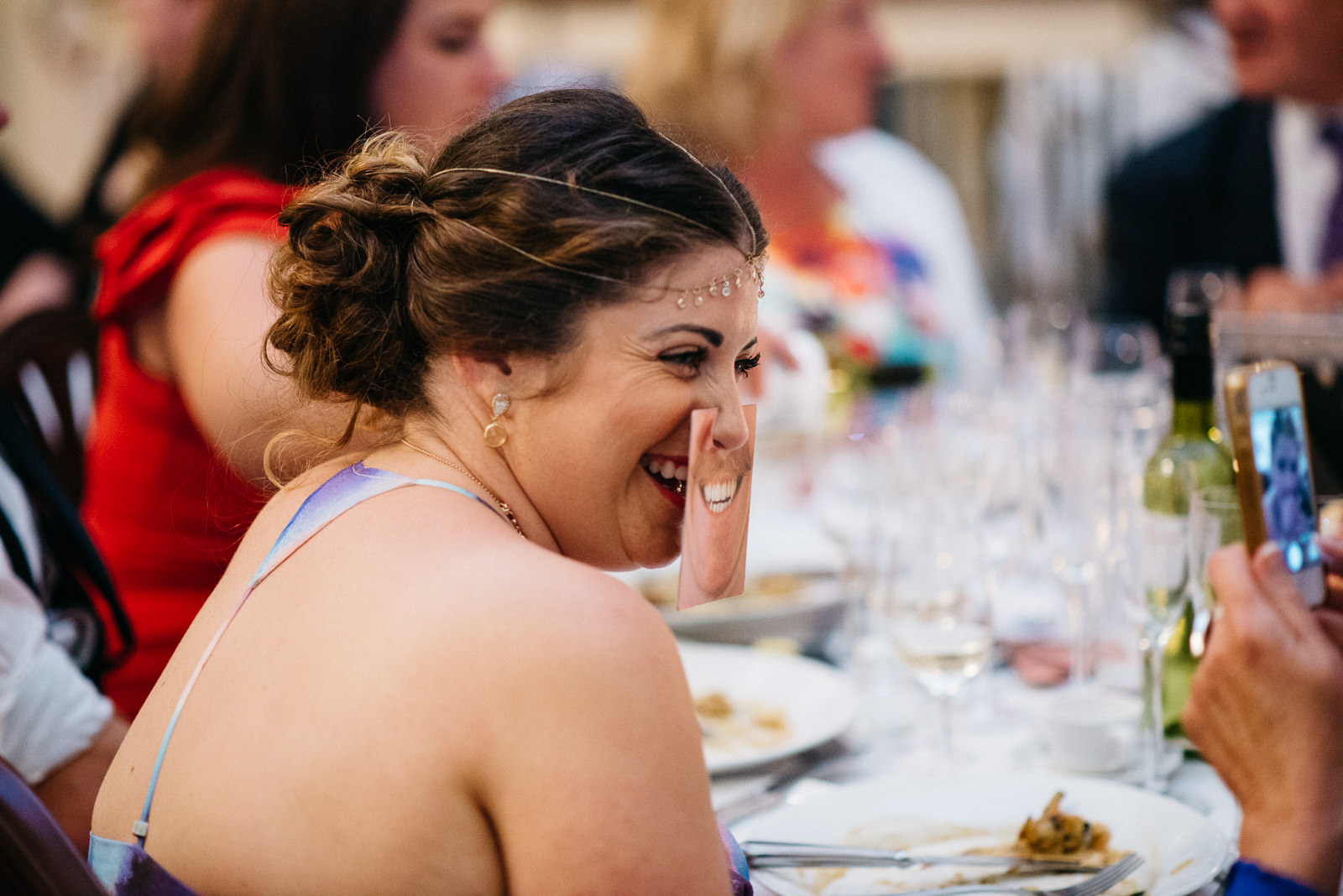 Guest using fun expression cards during wedding breakfast