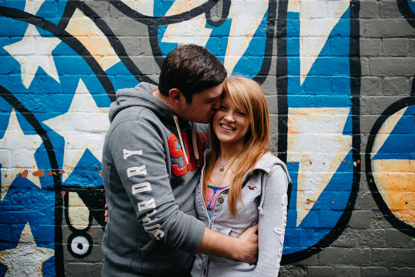 Lloyd cuddling Jo standing infront of graffiti behind Clwb Ifor Bach