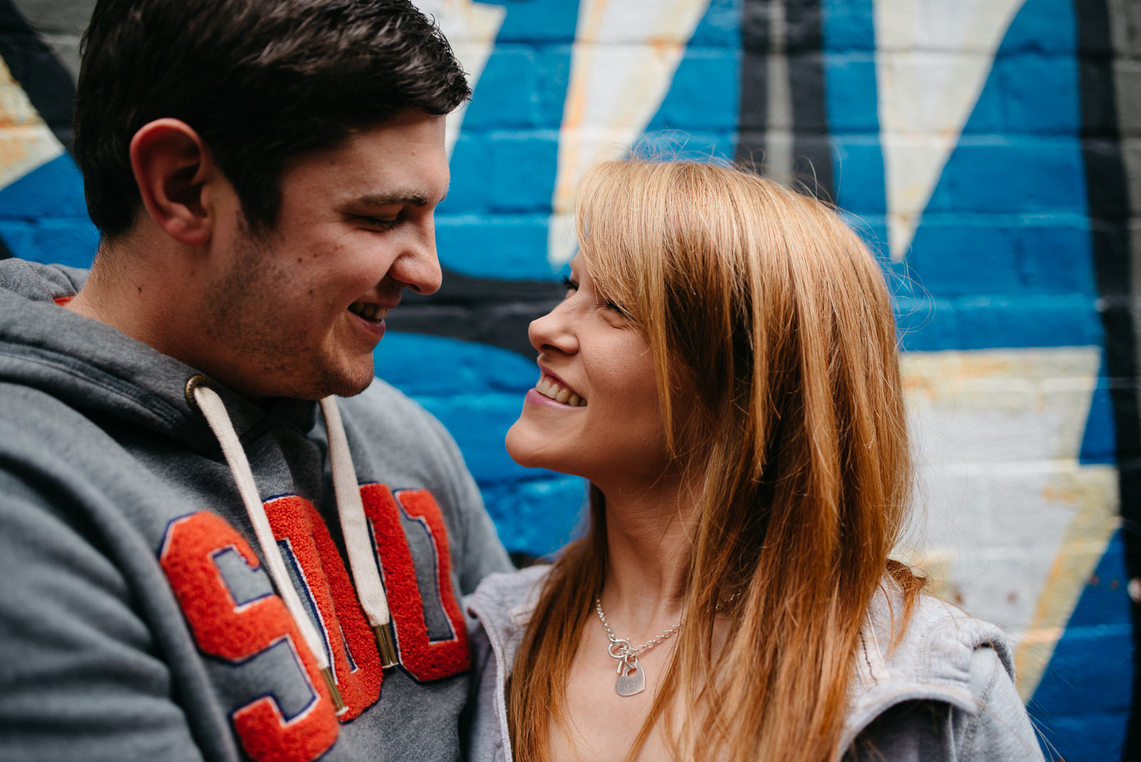 Jo & Lloyd looking at each other with graffiti backdrop during their city engagement session
