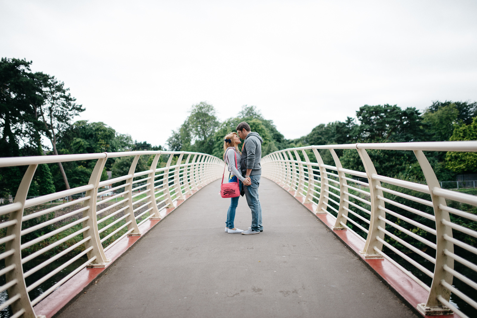 Leading lines running to couple standing on bride over River Taff during urban engagement session