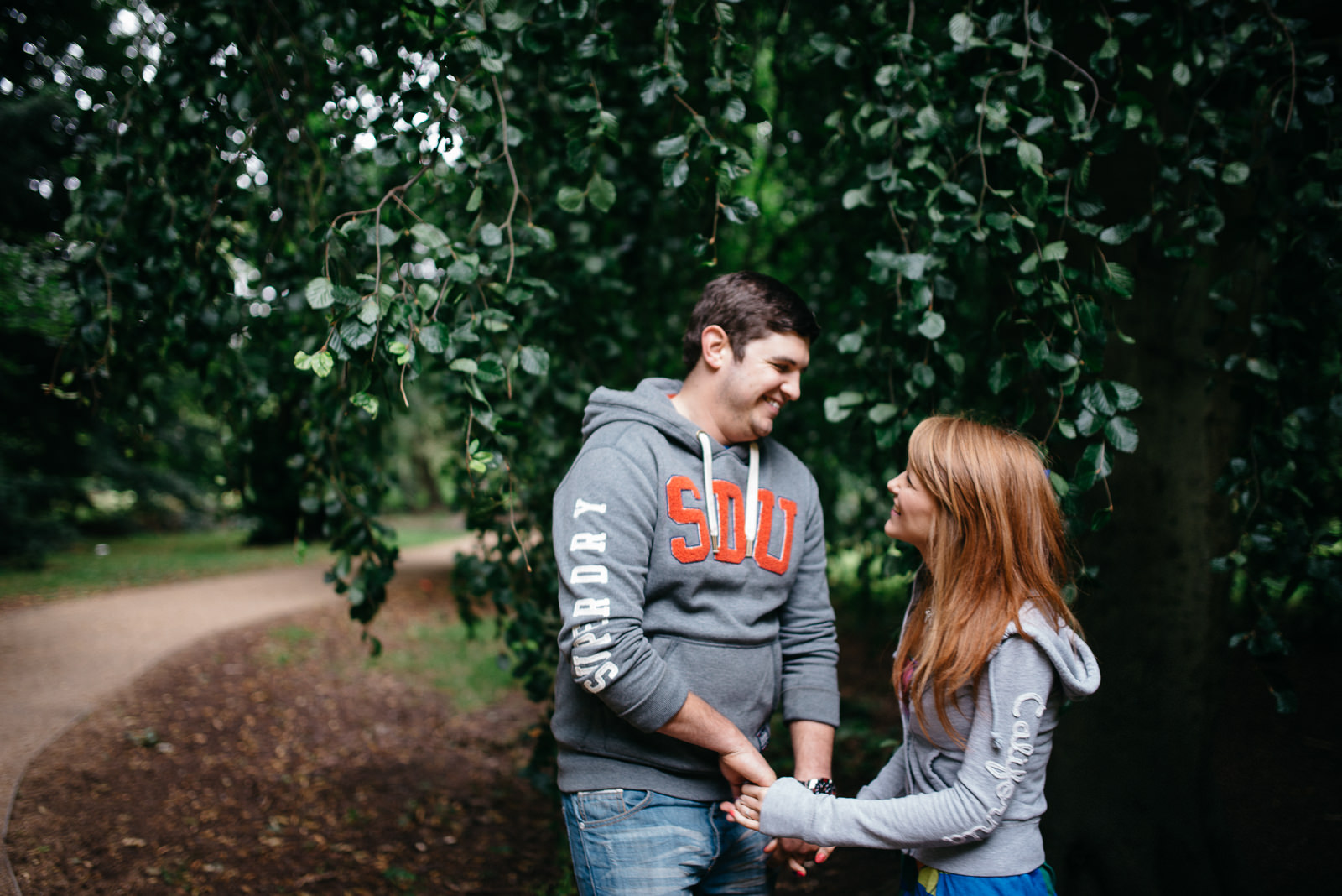 Jo & Lloyd laughing in Cardiff woodland engagement session