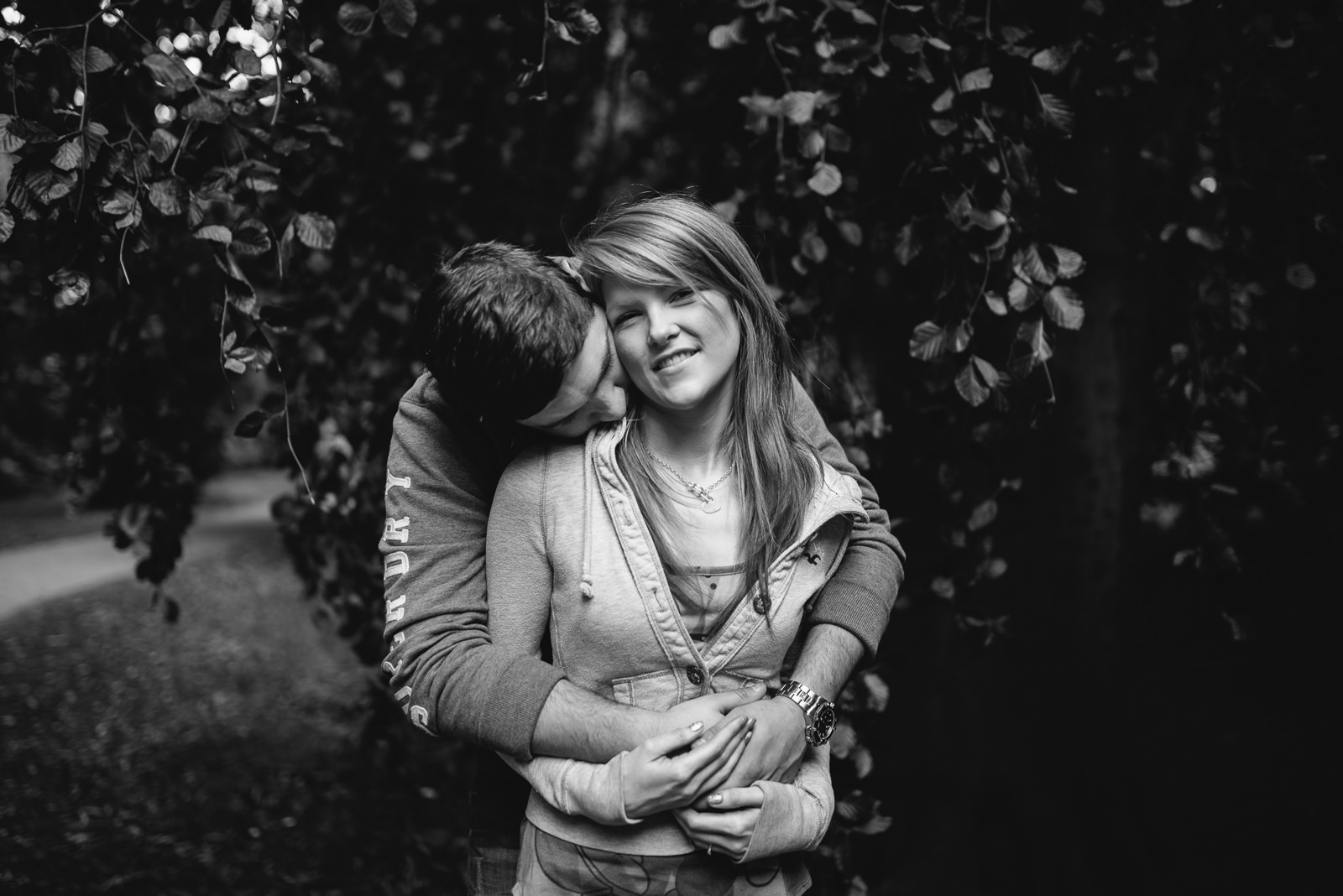 Black and white of happy bride to be with groom during woodland shoot
