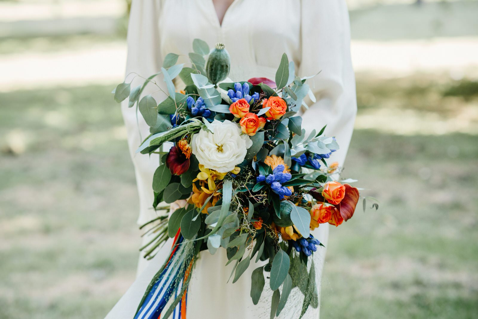 Beautiful modern handtied bouquet of blue white and yellow flowers by a florist