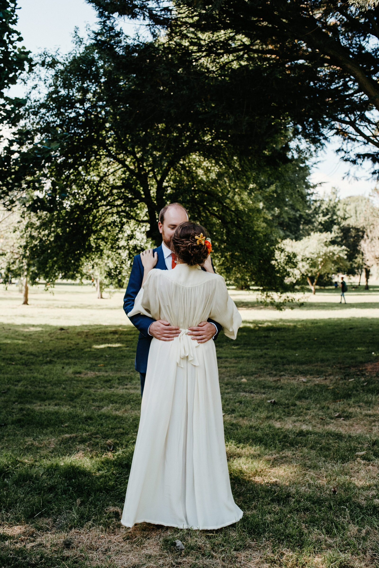 Portrait photograph of Jo & Rob, showing the back detail of the brides vintage gown which was her mothers