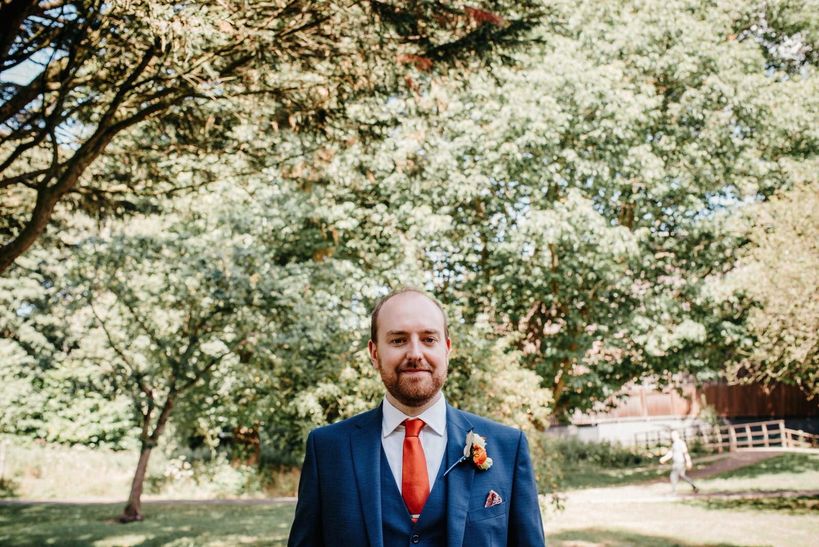 Groom wearing navy suit, orange tie and orange boutonniere outside the Royal College of Music and Drama