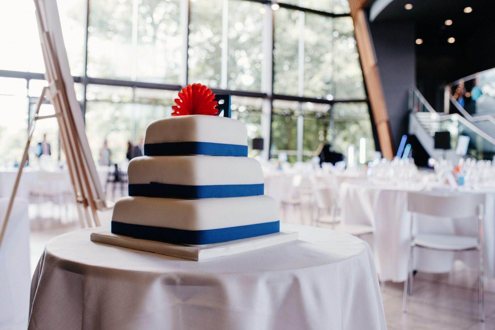 Simple square wedding cake with blue ribbon and orange origami decoration