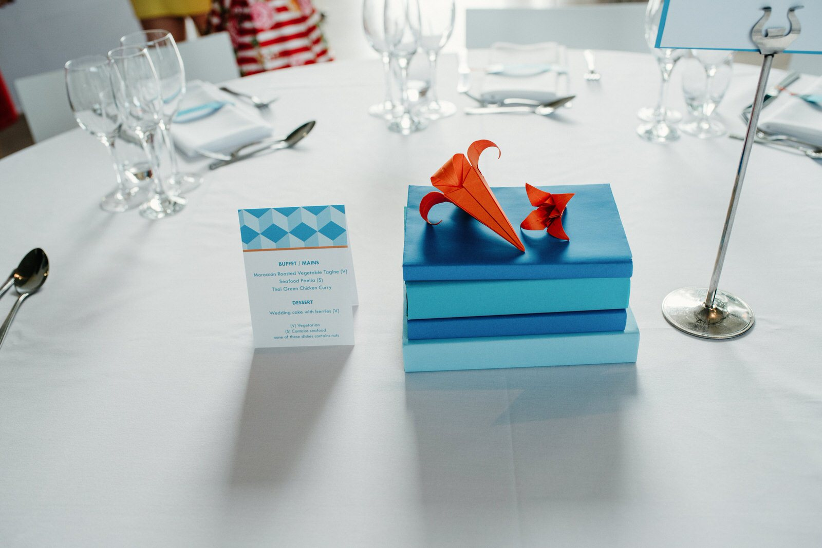 Colourful table decor details featuring paper origami details and books