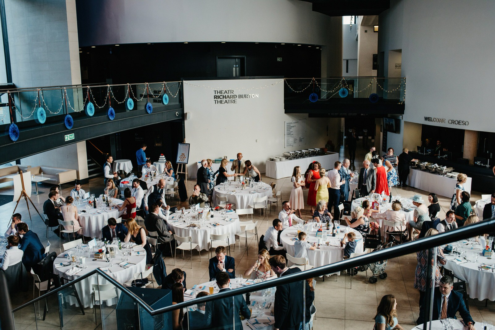 View of wedding guests from first floor at the Royal College of Music and Drama displaying blue fan decor and fairy lights
