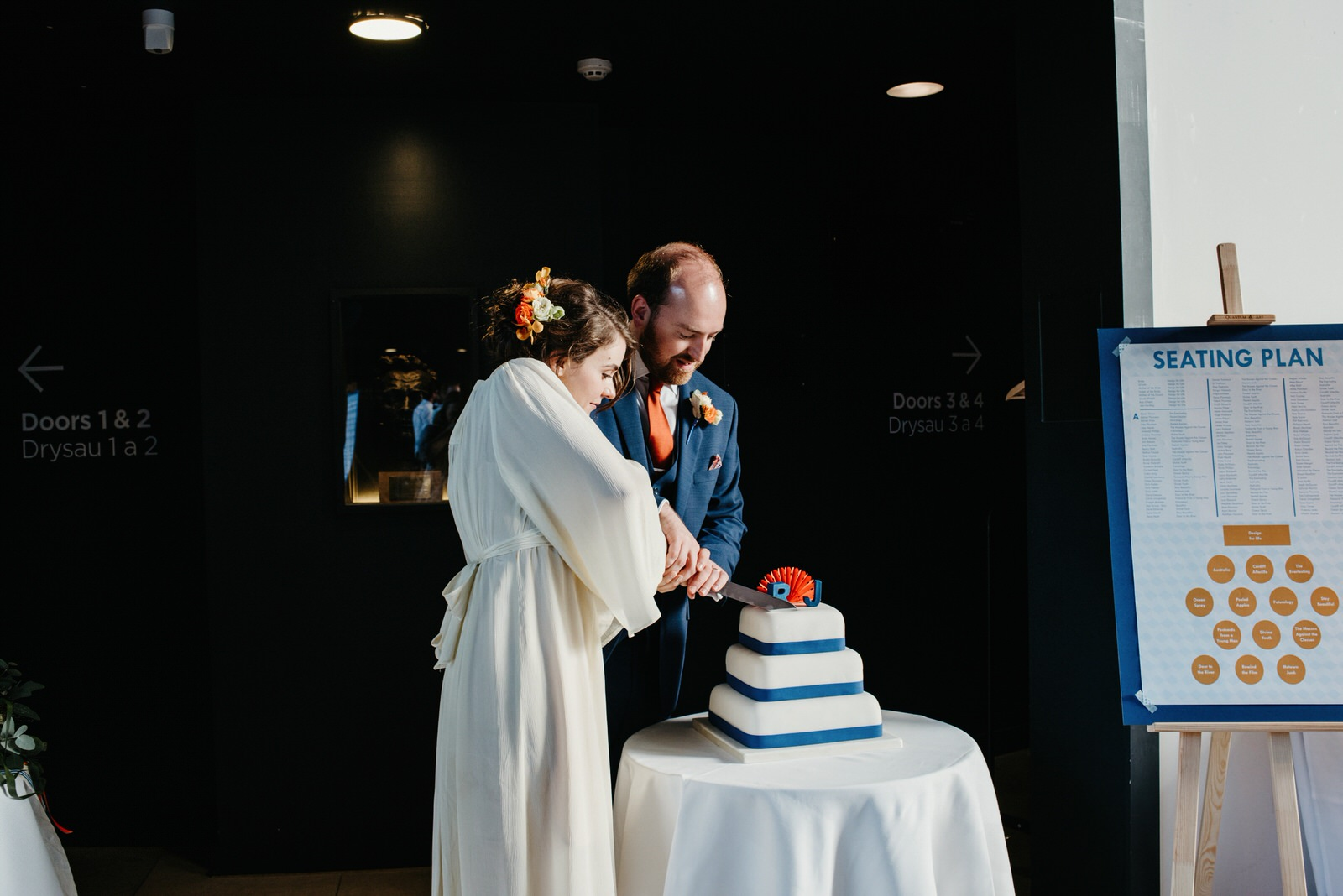 Bride and groom cutting simple cake with blue ribbon