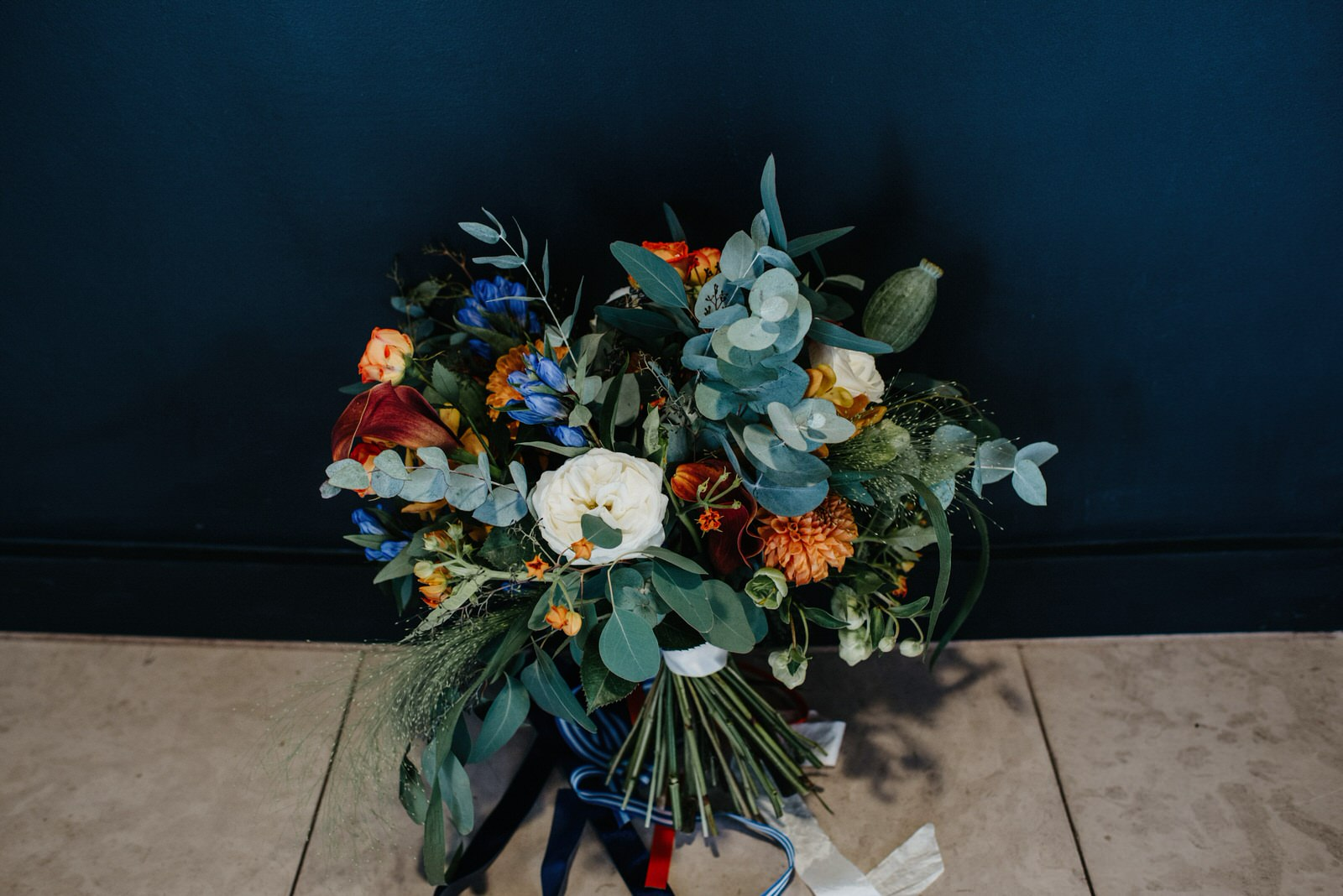 orange and blue wedding flowers with roses and eucalyptus