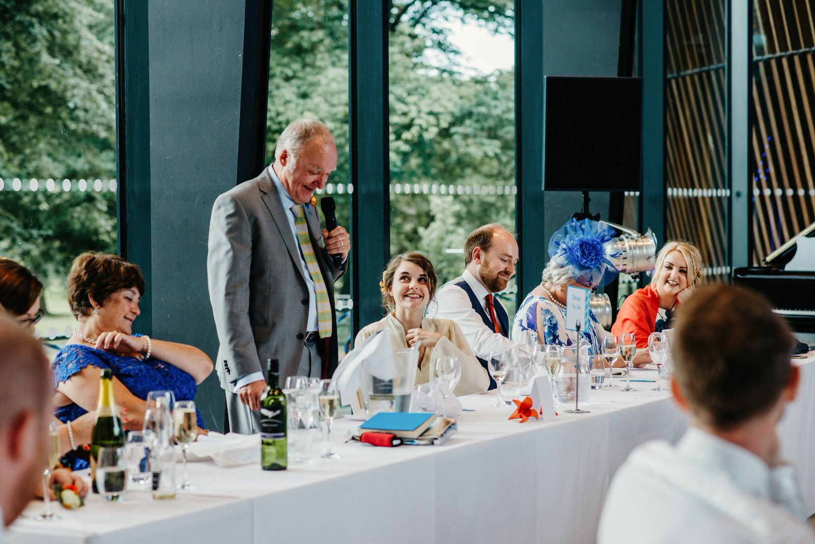 bride looking lovingly at her father while he delivers his speech during the wedding breakfast at the Royal College of Music and Drama