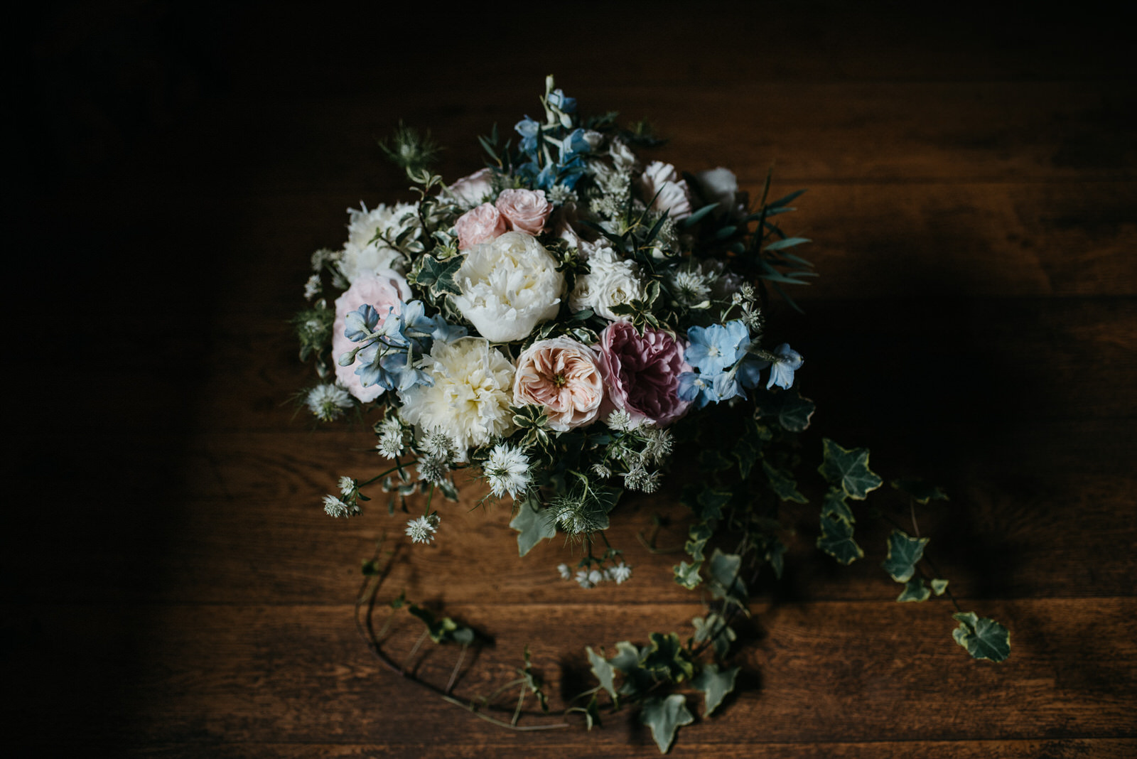 Moody photograph of pastel handtied bouquet with David Austin roses and Ivy arranged by Shropshire florist