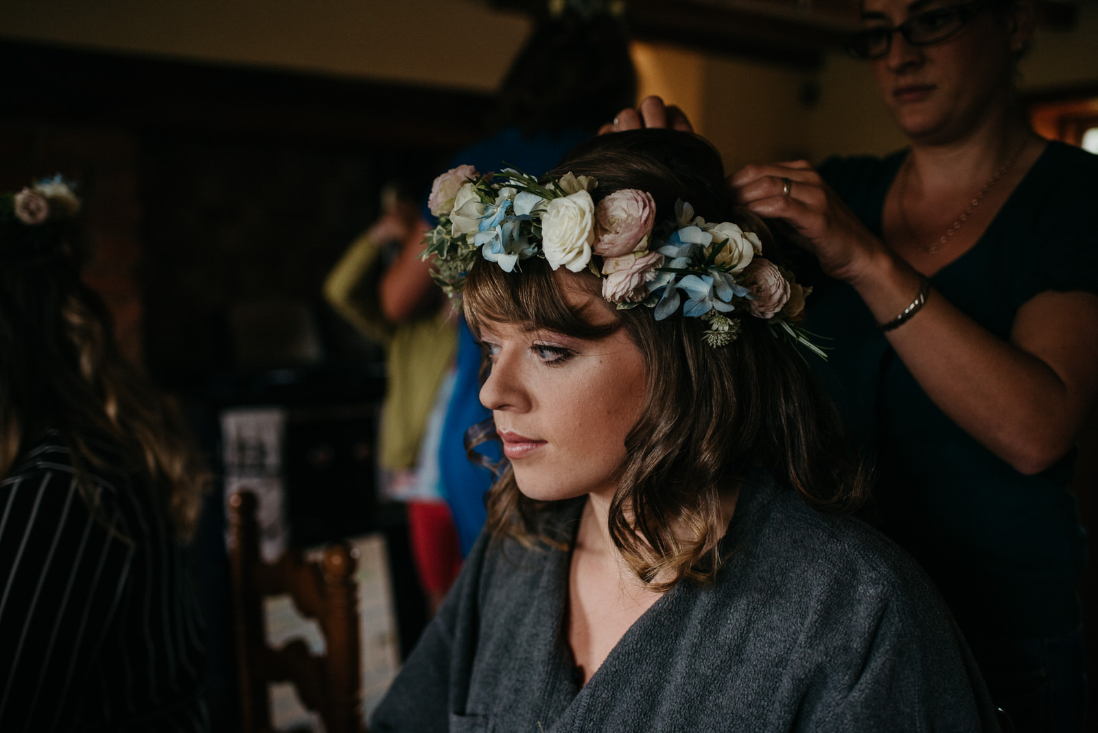 Moody portrait of bride wearing her pastel floral crown during preparations at her Shropshire home
