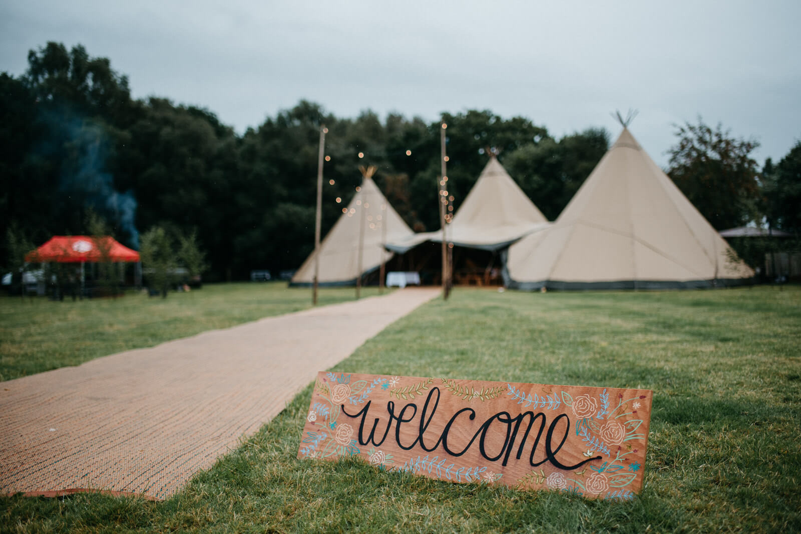 Wooden 'welcome' sign infront of tipi with festoon lit hessian jute walkway at relaxed Shropshire wedding