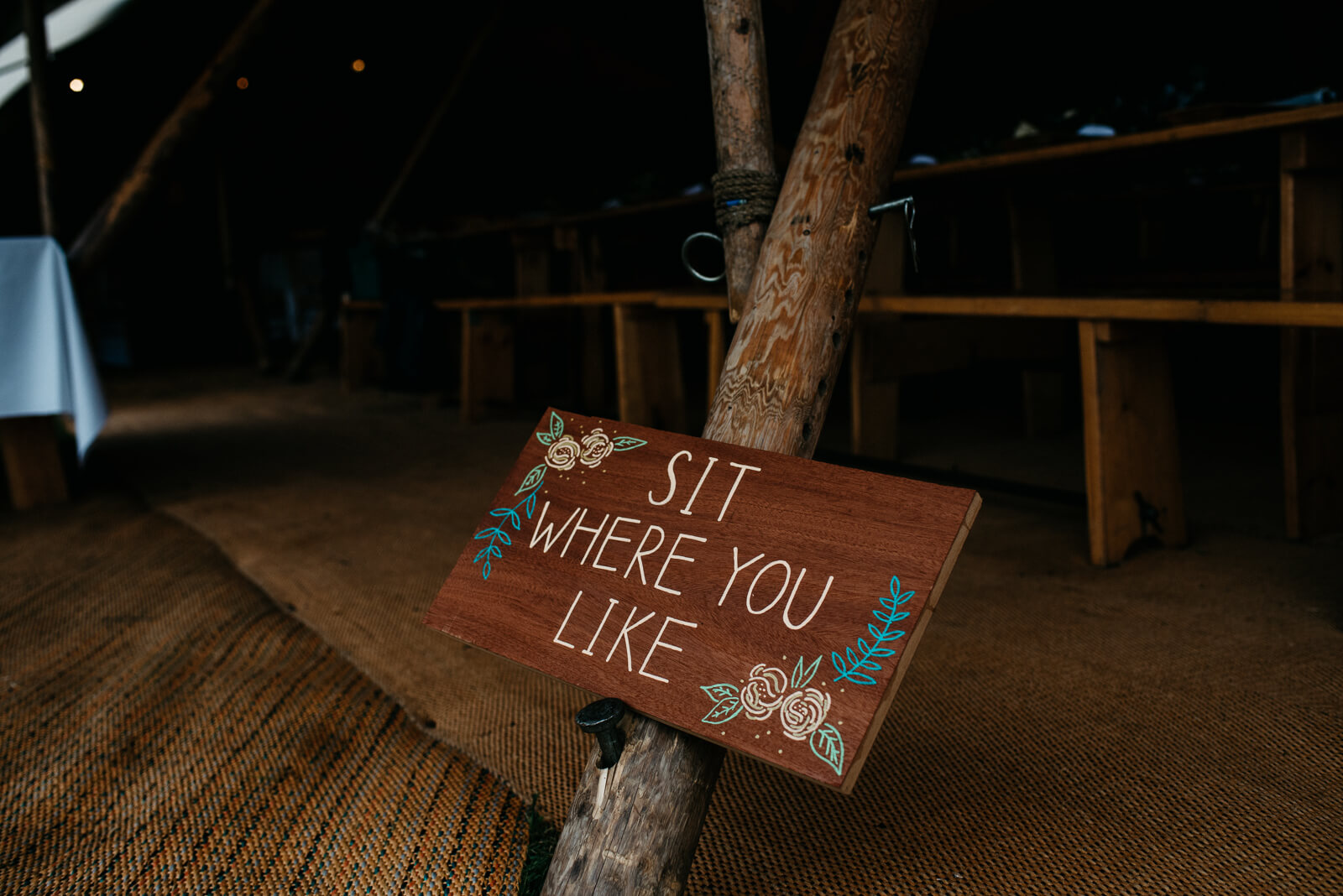 Wooden tipi signage encouraging guests to sit where they like at a Shropshire festival wedding