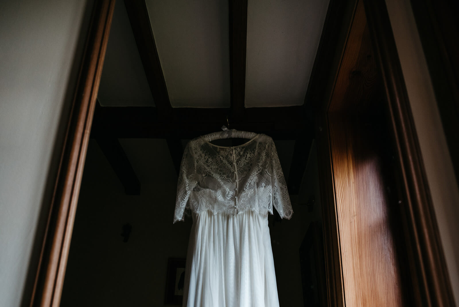 Moody detail photograph of brides lace dress handing in old farm house Shropshire home