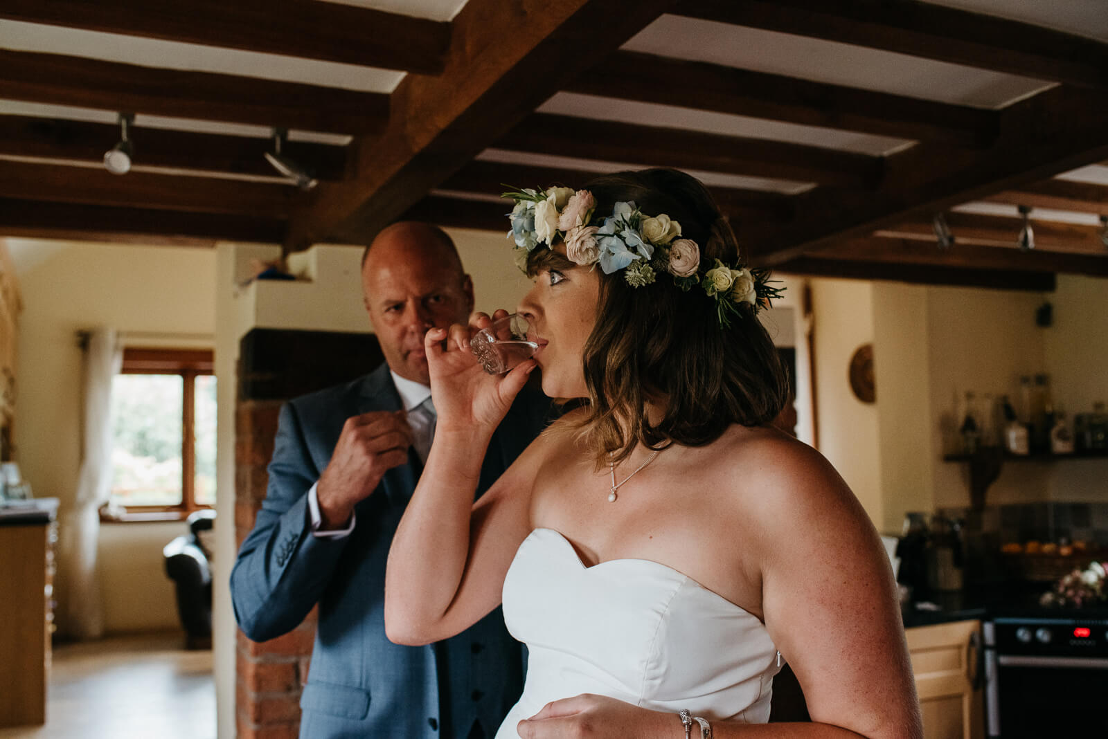 Bride steading her nerves with a shot of Vodka with her dad before her Shropshire wedding