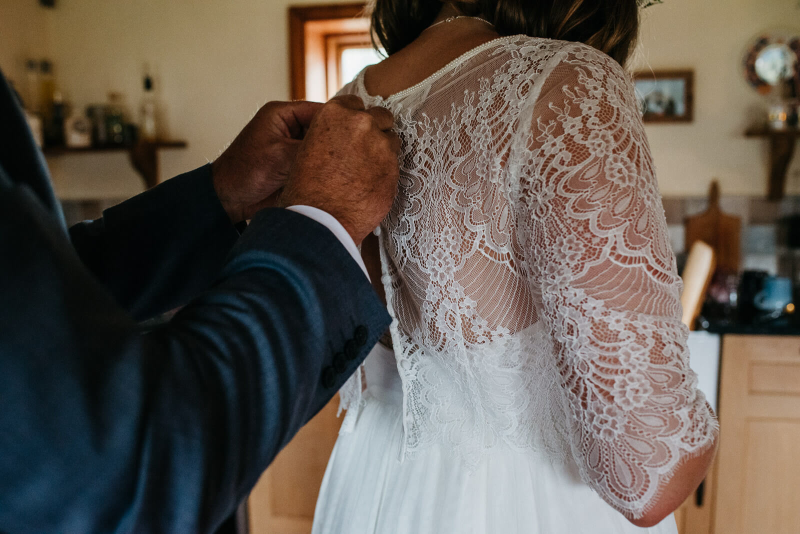 Father of the bride buttoning her lace overlay at his Shropshire home before her boho festival wedding