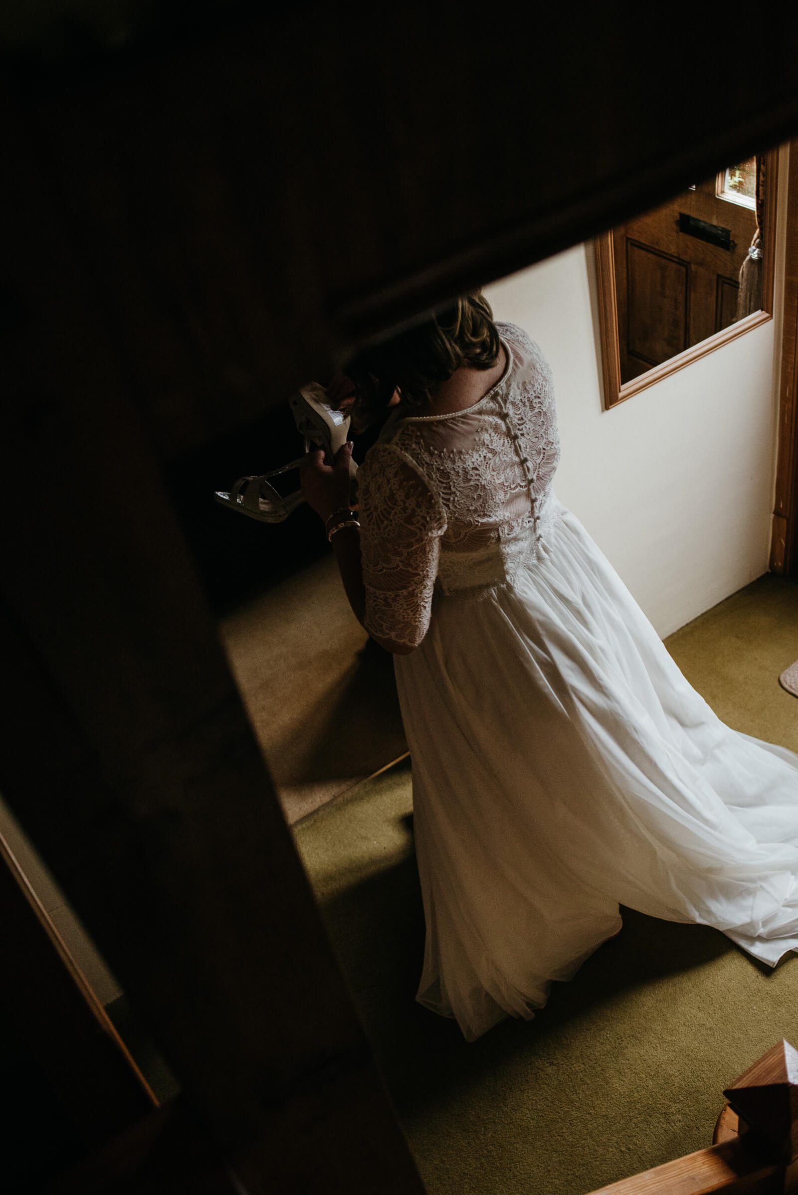 Moody portrait of bride in her simple tule and lace dress on stairs