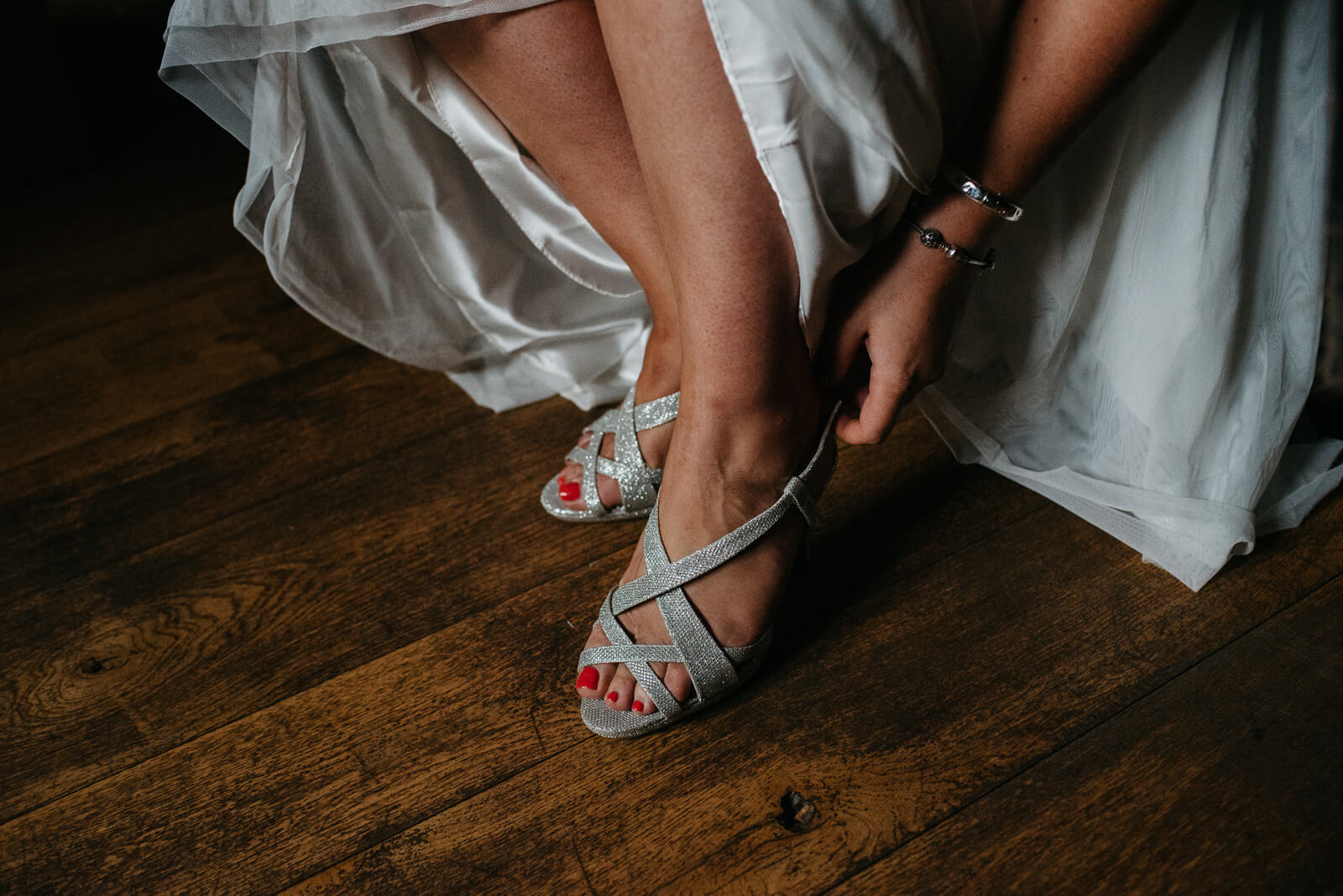 Moody portrait of bride putting on her sparkley Jimmy Choo shoes at their Shropshire home