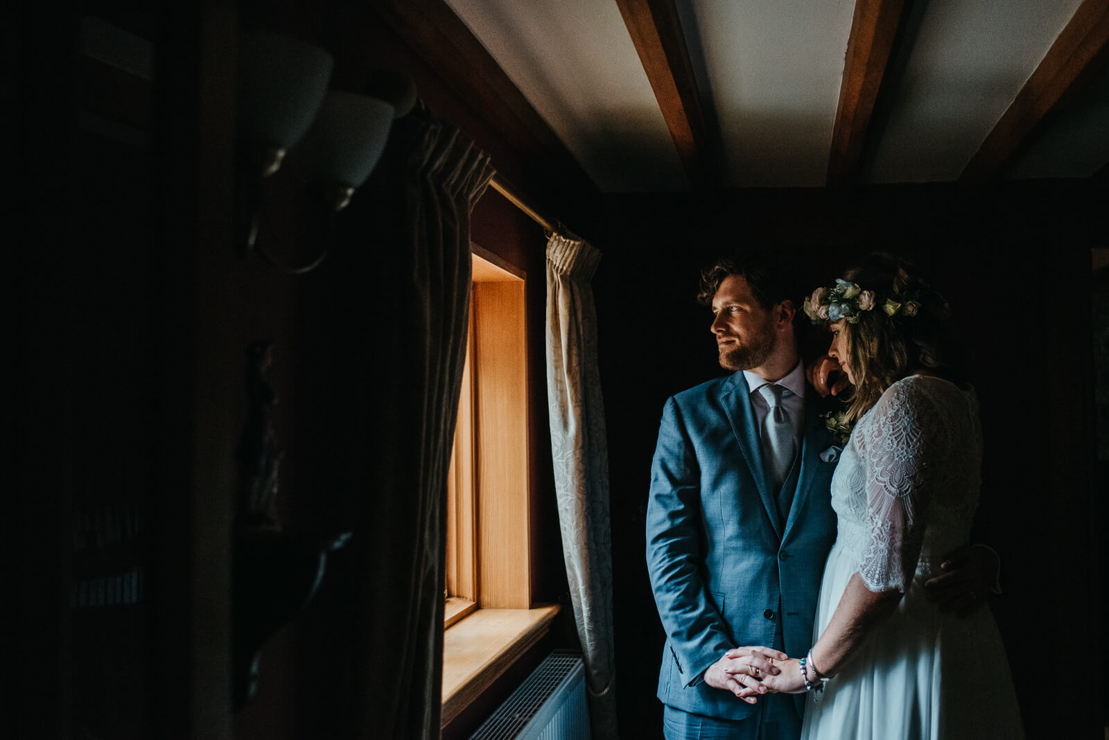 Moody portrait of bride and groom in front of window at woodland tipi wedding in Shropshire