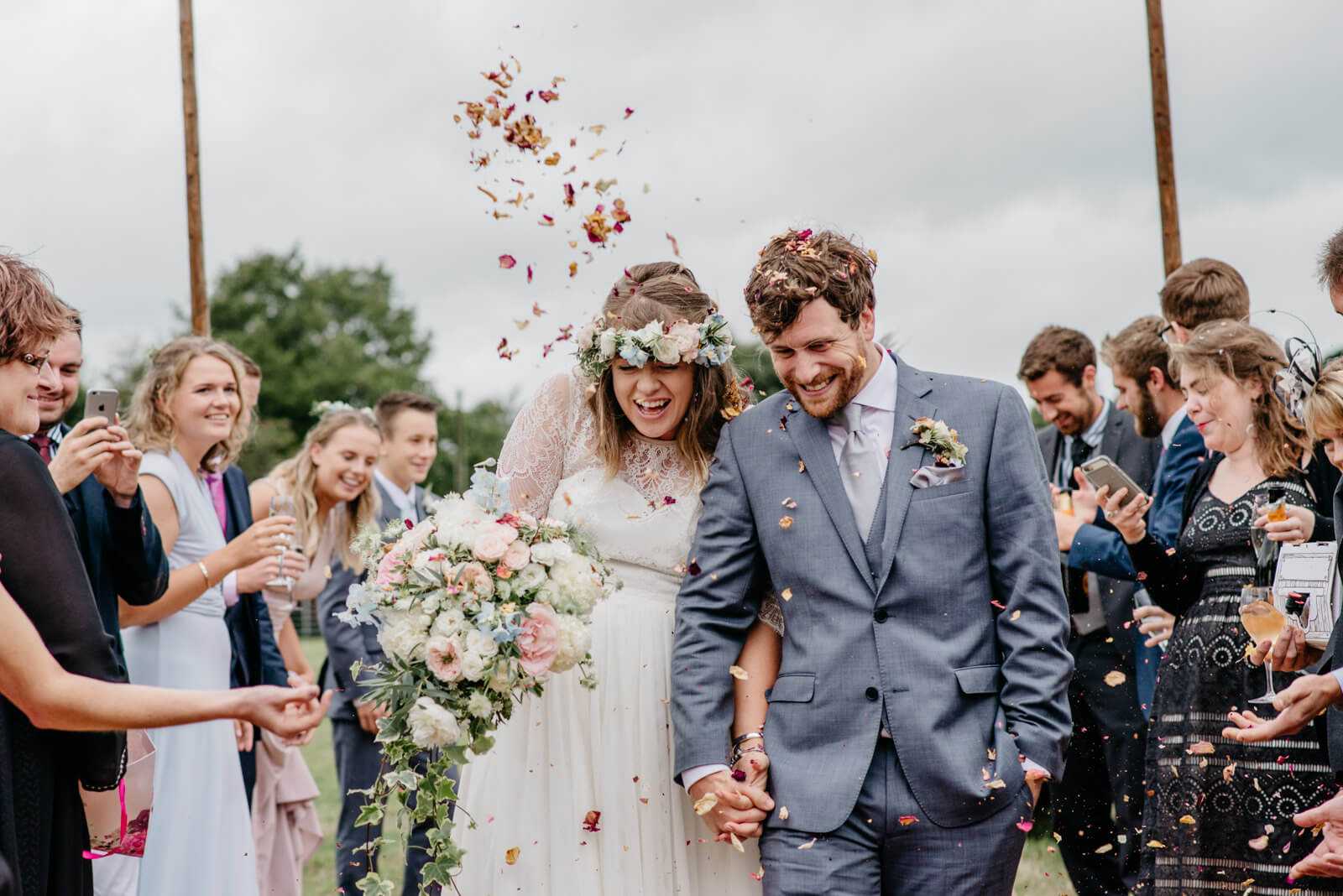 Bride wearing floral crown and groom passing through confetti gauntlet on their way to Shropshire tipi wedding reception