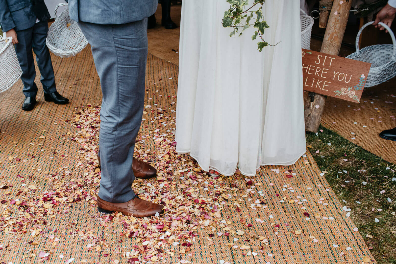 Bride and groom standing in puddle of homemade flower petal confetti at tipi wedding near Wrexham