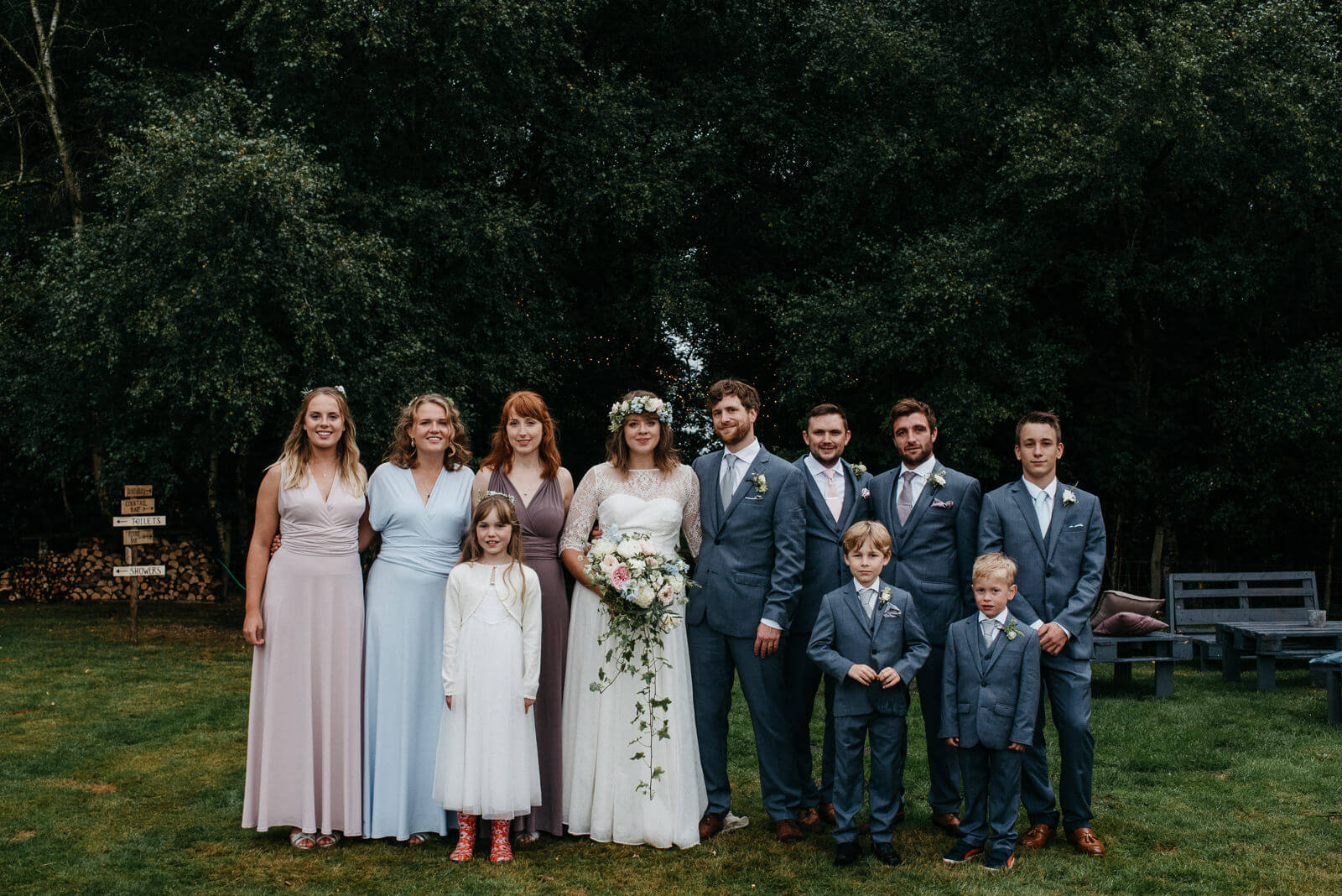 Bridal party of bridesmaids in two birds style mismatched dressed and boho bride at Shropshire wedidng
