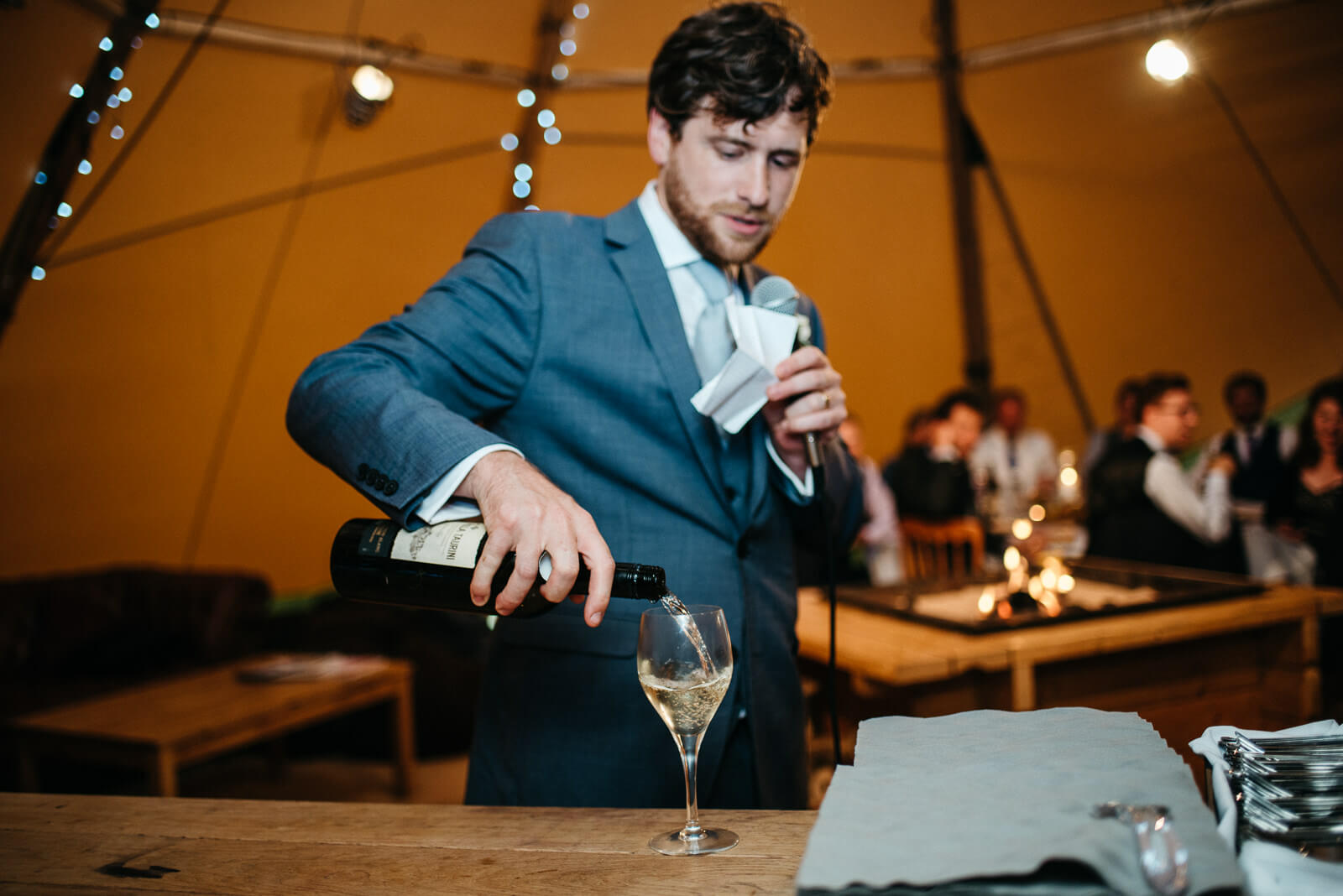Groom pouring himself a drink in wedding tipi to steady the nerves before his wedding speech