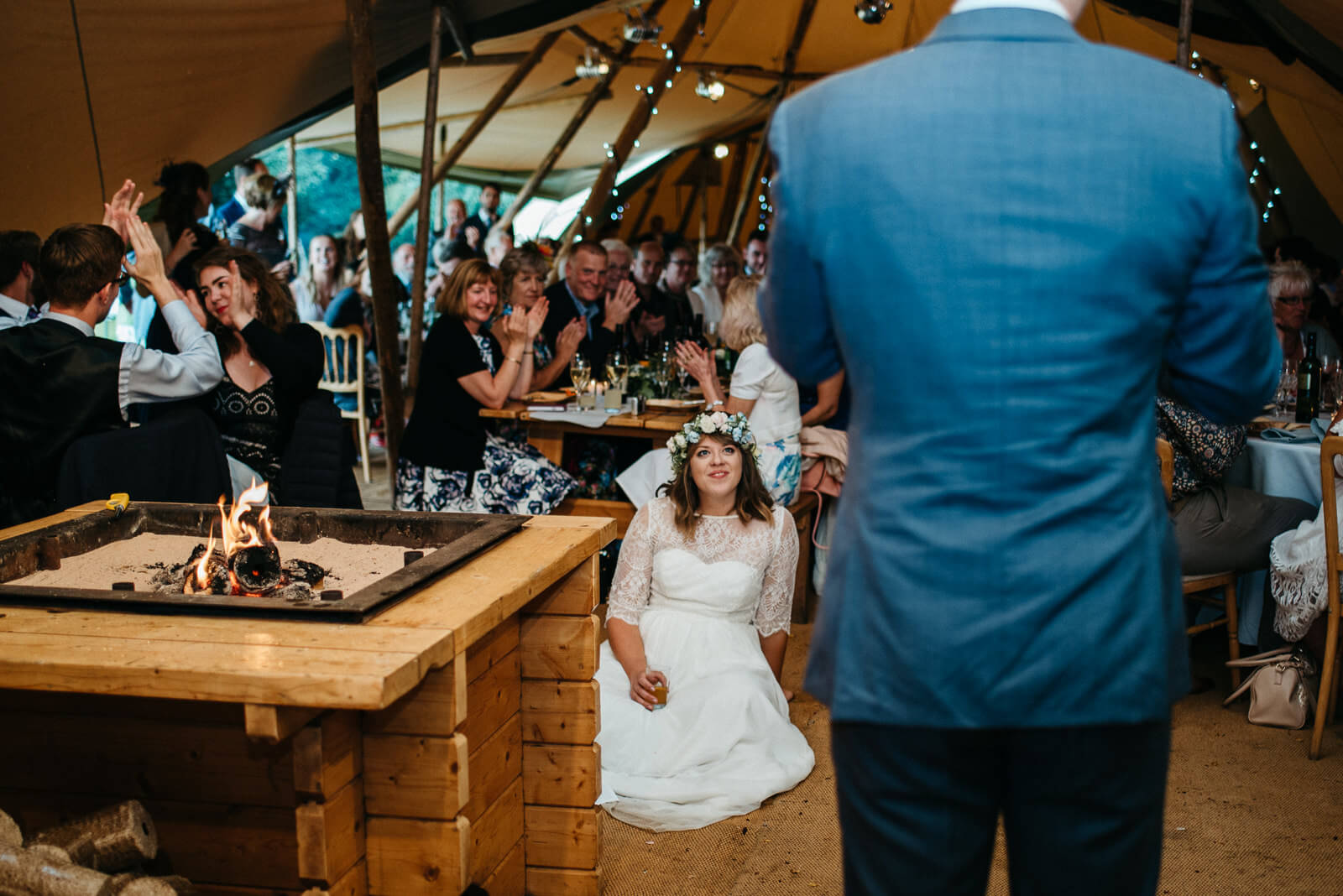Relaxed bride sitting on tipi floor watching her husband speak to wedding guests at boho wedding