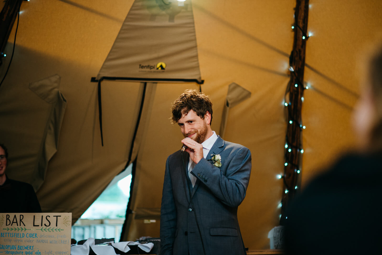 Groom in tipi during his speech at wedding on the edge of Shropshire nature reserve