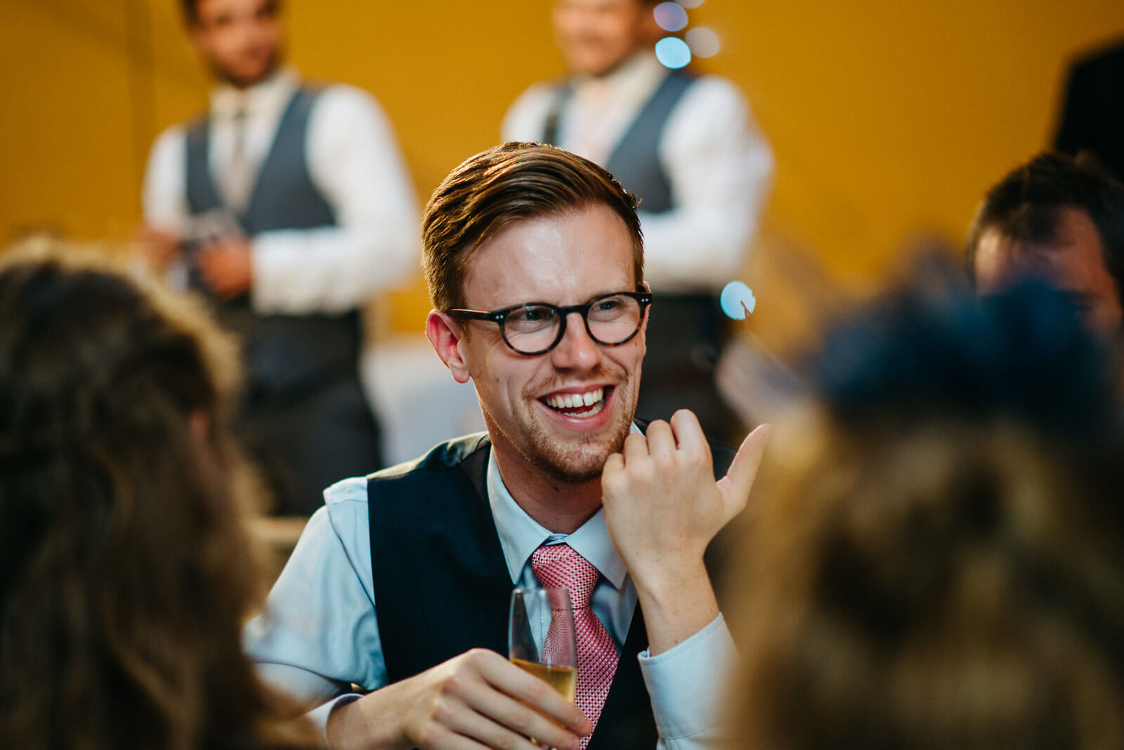 Male guest laughing during speeches at Shropshire festival wedding