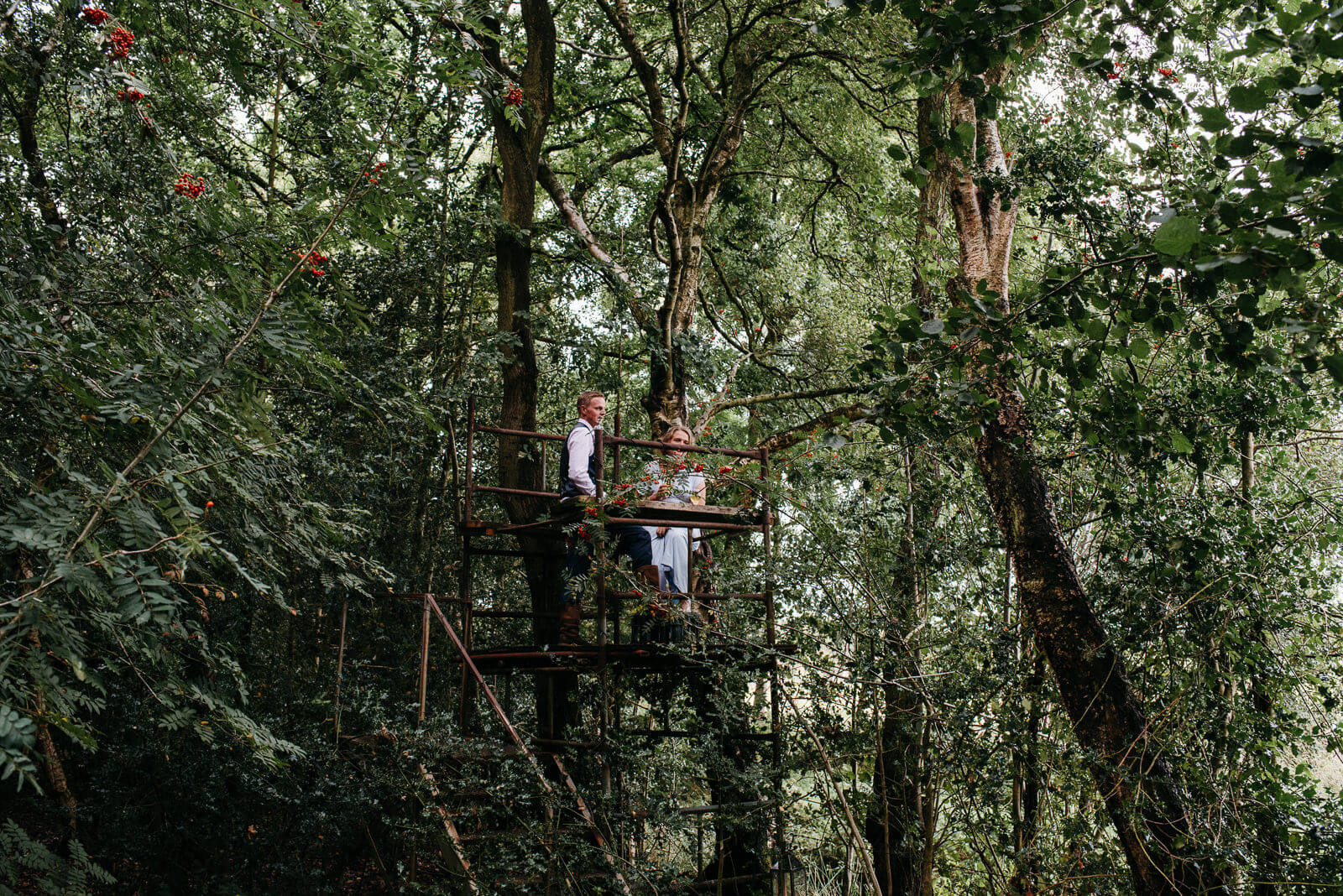 Wedding guests enjoying the woodland tree house at a Shropshire festival wedding