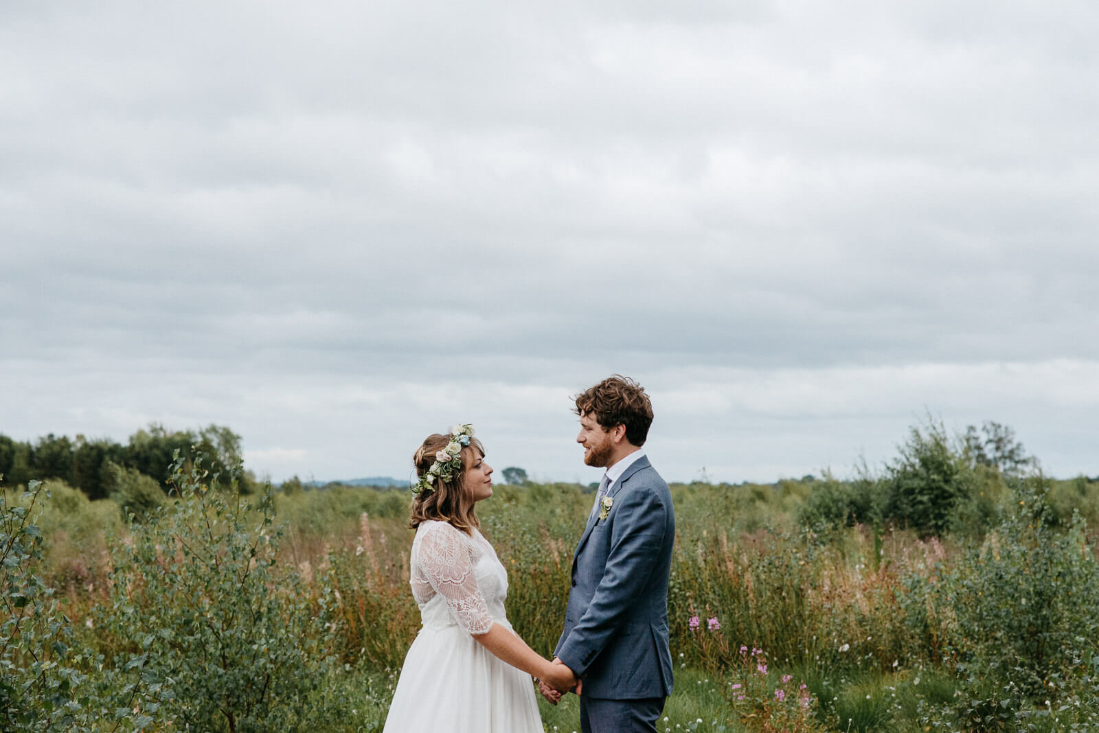 Relaxed portrait of boho bride wearing floral crown and stylish groom on edge of nature reserve mosses in Shropshire