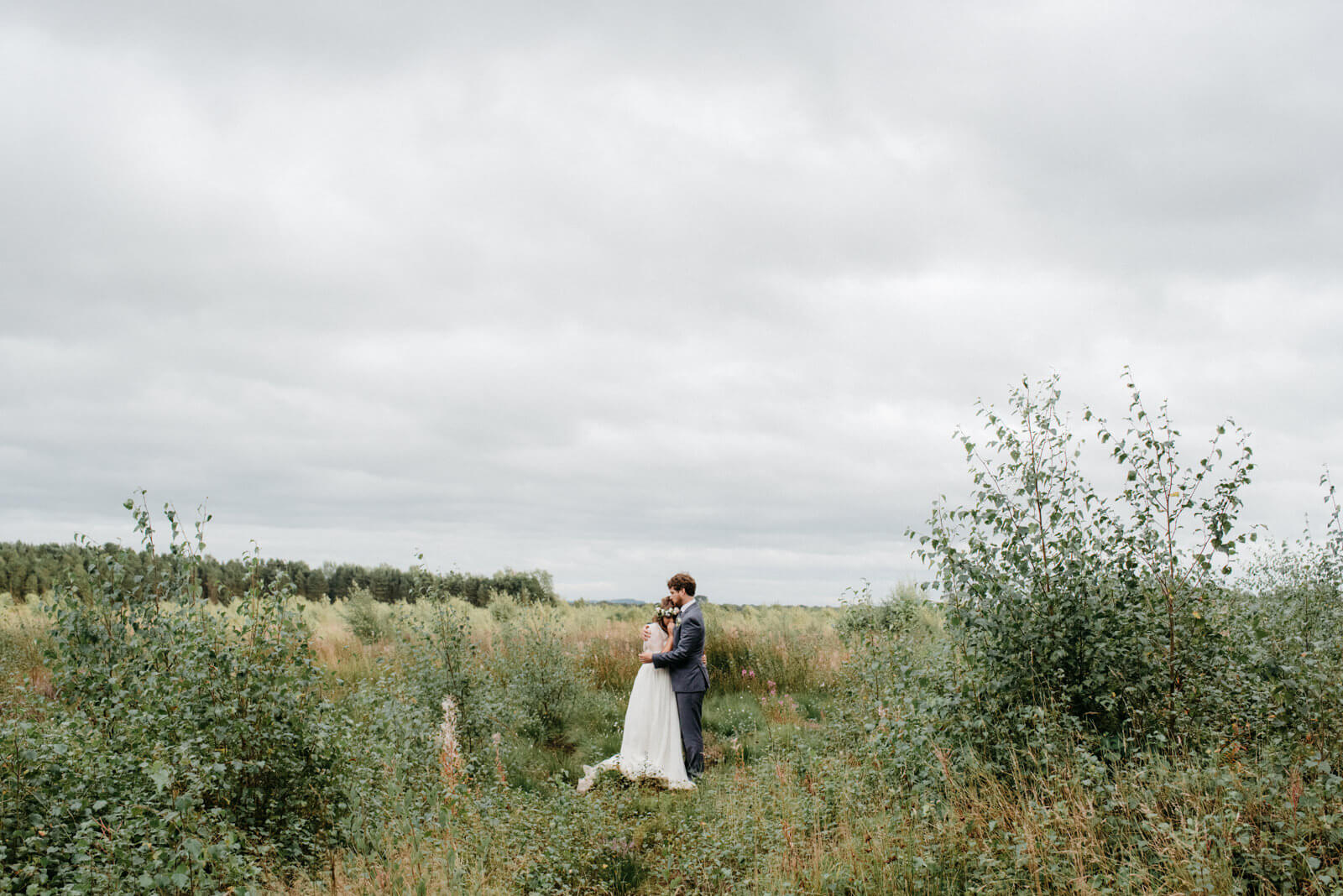 relaxed portrait of boho bride and groom in Fenn's, Whixall and Bettisfield Mosses National Nature Reserve at festival wedding