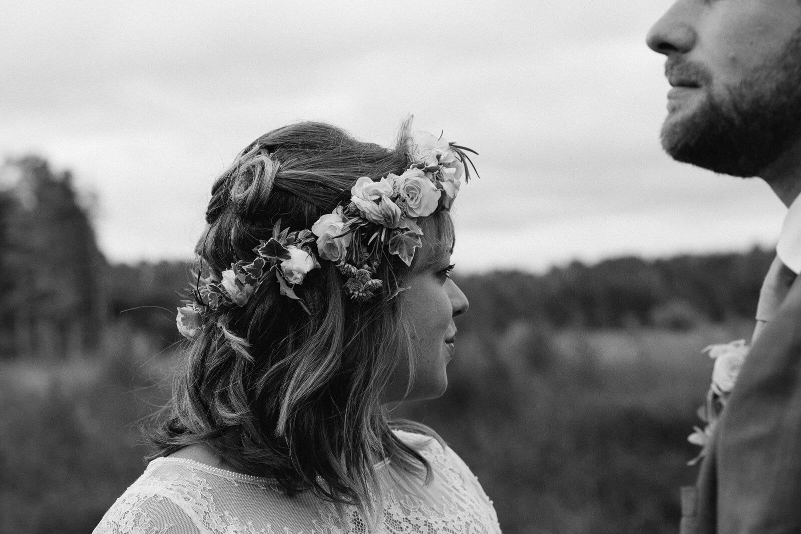 Black and white photograph of floral crown wearing bride looking out into the wilderness