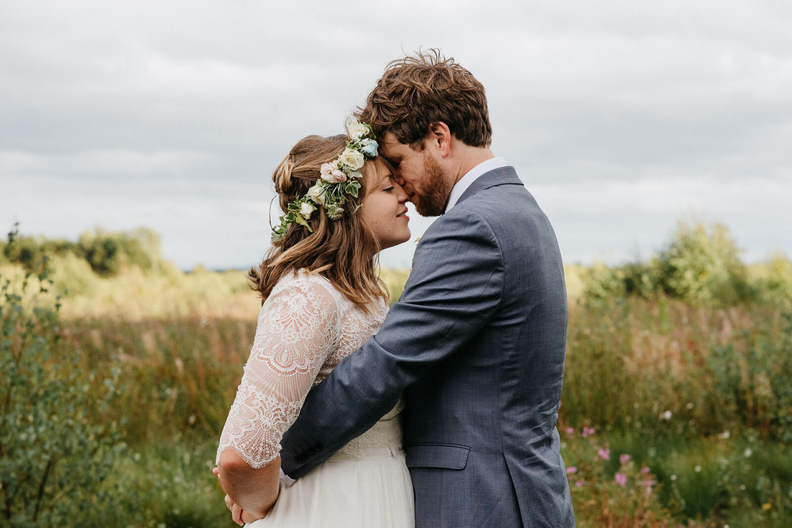 Bride and groom in a tender embrace during their portraits on the edge of the Fenn's, Whixall and Bettisfield Mosses National Nature Reserve