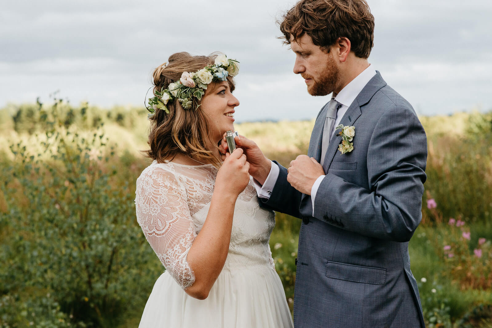 Shropshire Bride wearing floral crown looking lovingly at groom while holding his hipflask at tipi festival wedding on the edge of a nature reserve