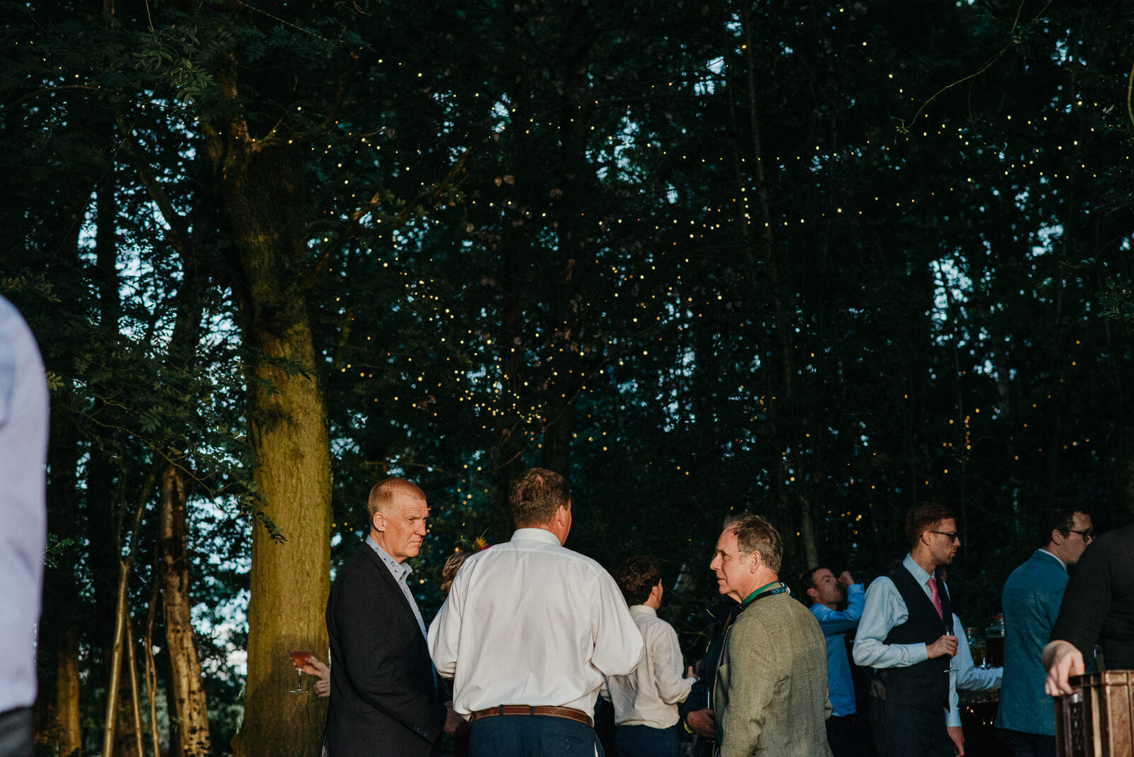 Guests chatting under fairy lit light tree canopy at Shropshire festival wedding