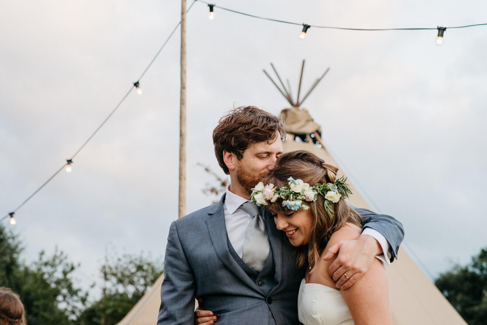 Groom lovingly kisses bride wearing floral crown under festoon lights at festival style Shropshire wedding